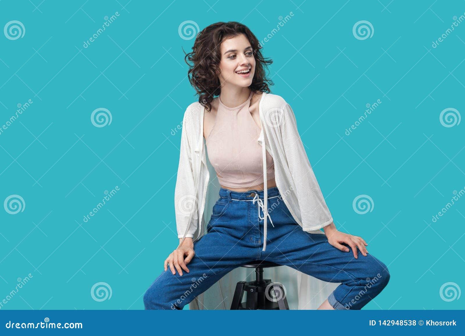 Portret van gelukkige succesvolle tevreden mooie jonge donkerbruine vrouw in toevallige stijlzitting op stoel, het toothy glimlac