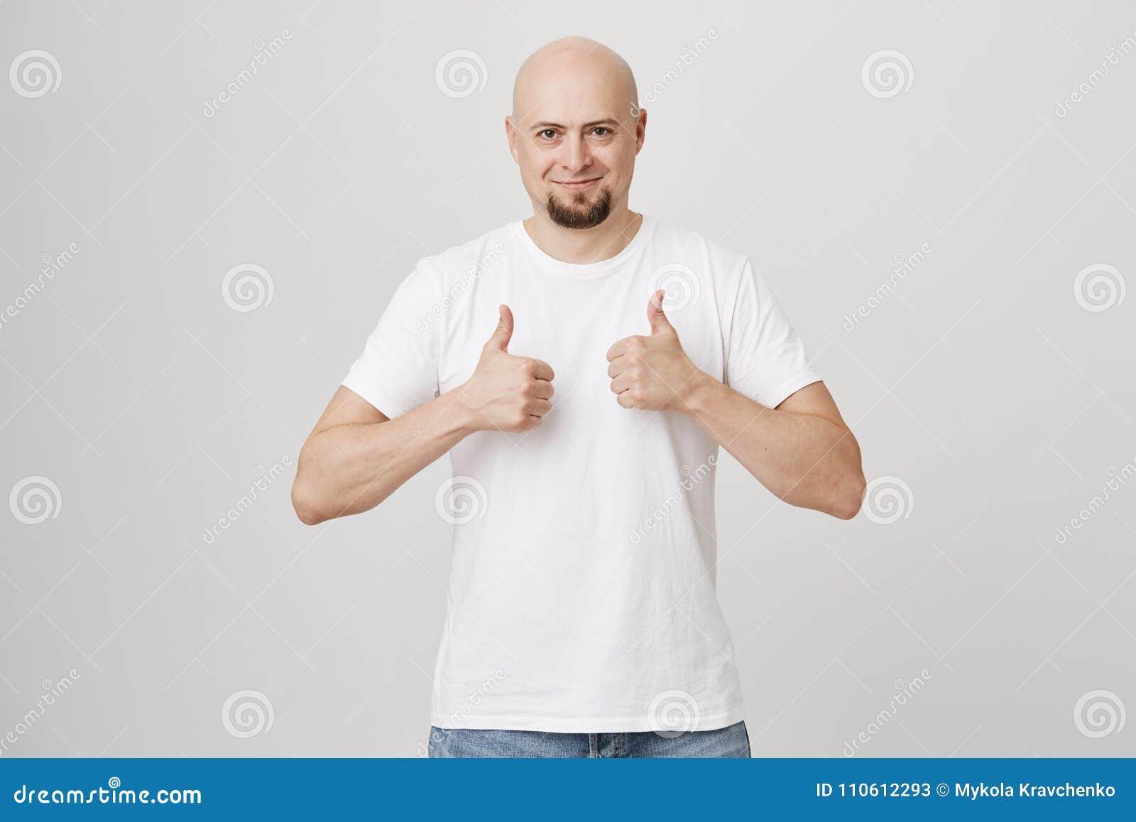 Portret van gelukkige tevreden kale gebaarde duimen tonen en kerel die, zijnd tevreden met punt dat hij, status heeft gekocht gli