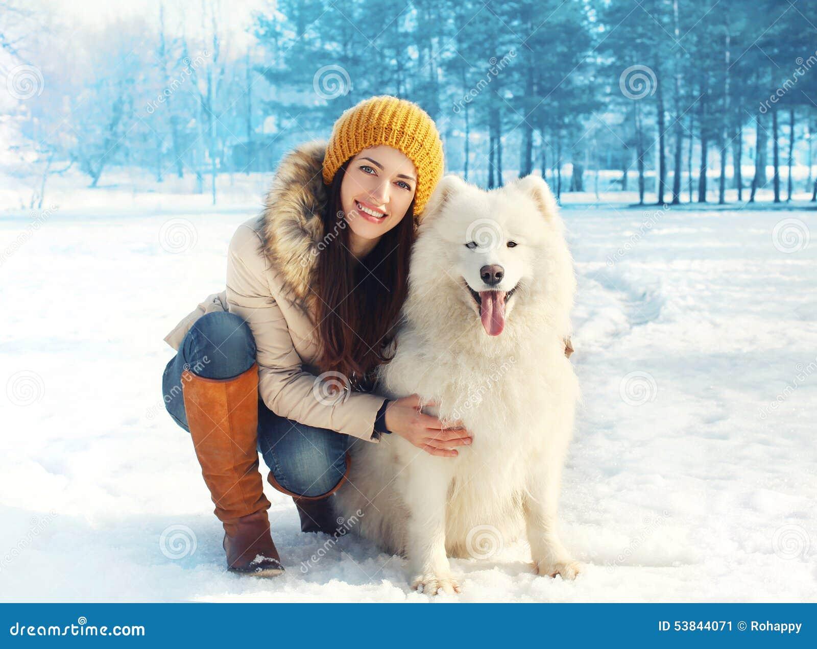 Portret van gelukkige vrouw met witte Samoyed-hond in openlucht