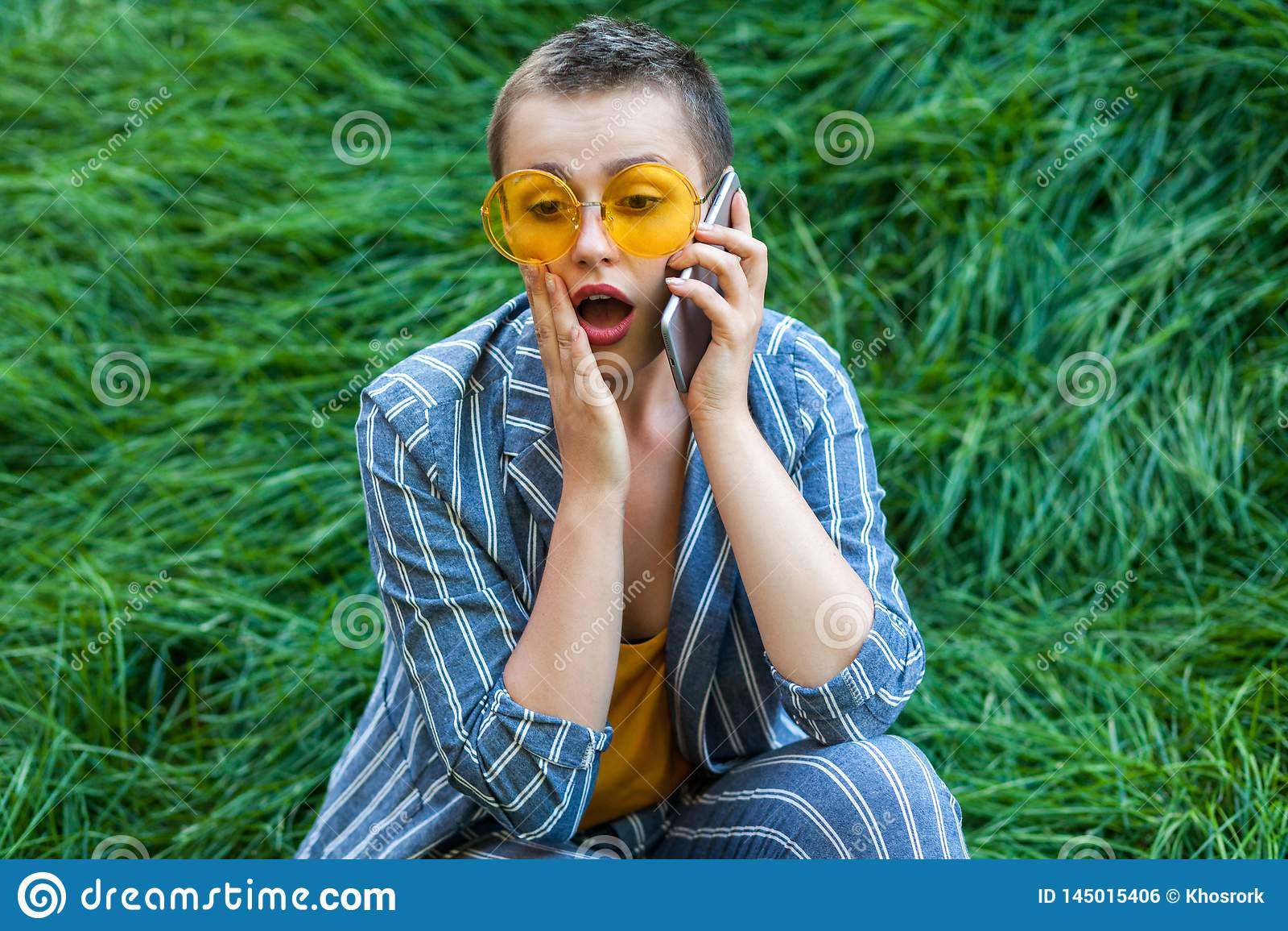 Portret van geschokte leuke jonge korte haarvrouw die in toevallig blauw gestreept kostuum, gele overhemd en glazen op groen gras