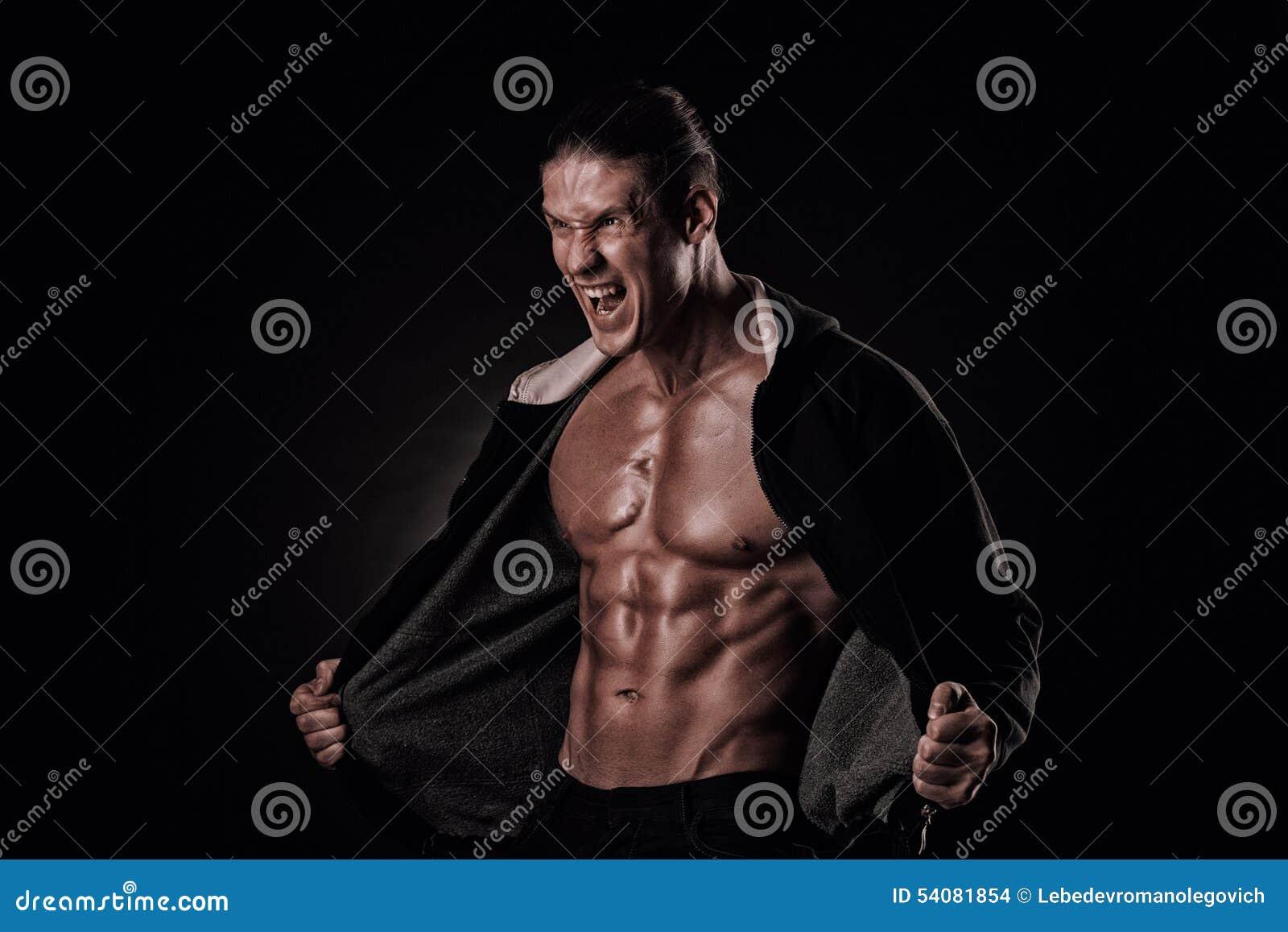 Portret van gillende bodybuilder met strakke spieren en zijn mou