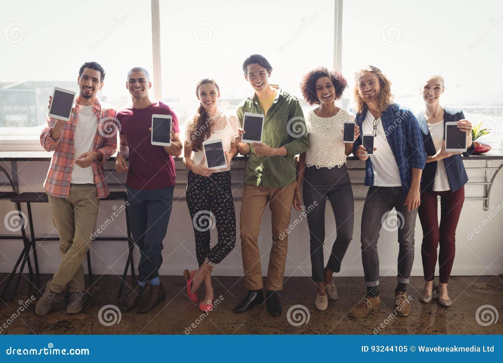 Portret van glimlachend commercieel team die technologieën tonen op creatief kantoor