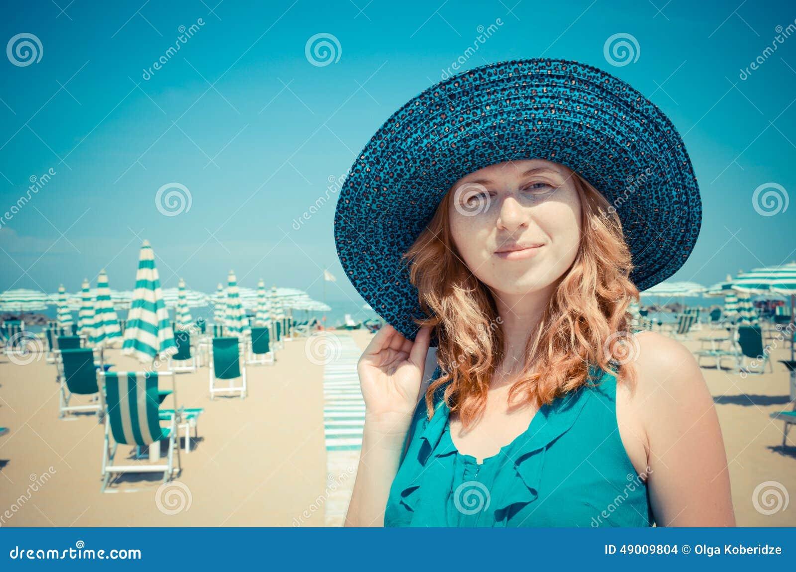 Portret van glimlachend roodharig meisje in hoed op de kust