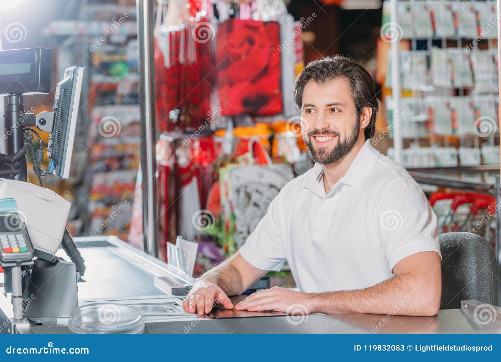 Portret van glimlachende mannelijke winkelmedewerker op contant geldpunt