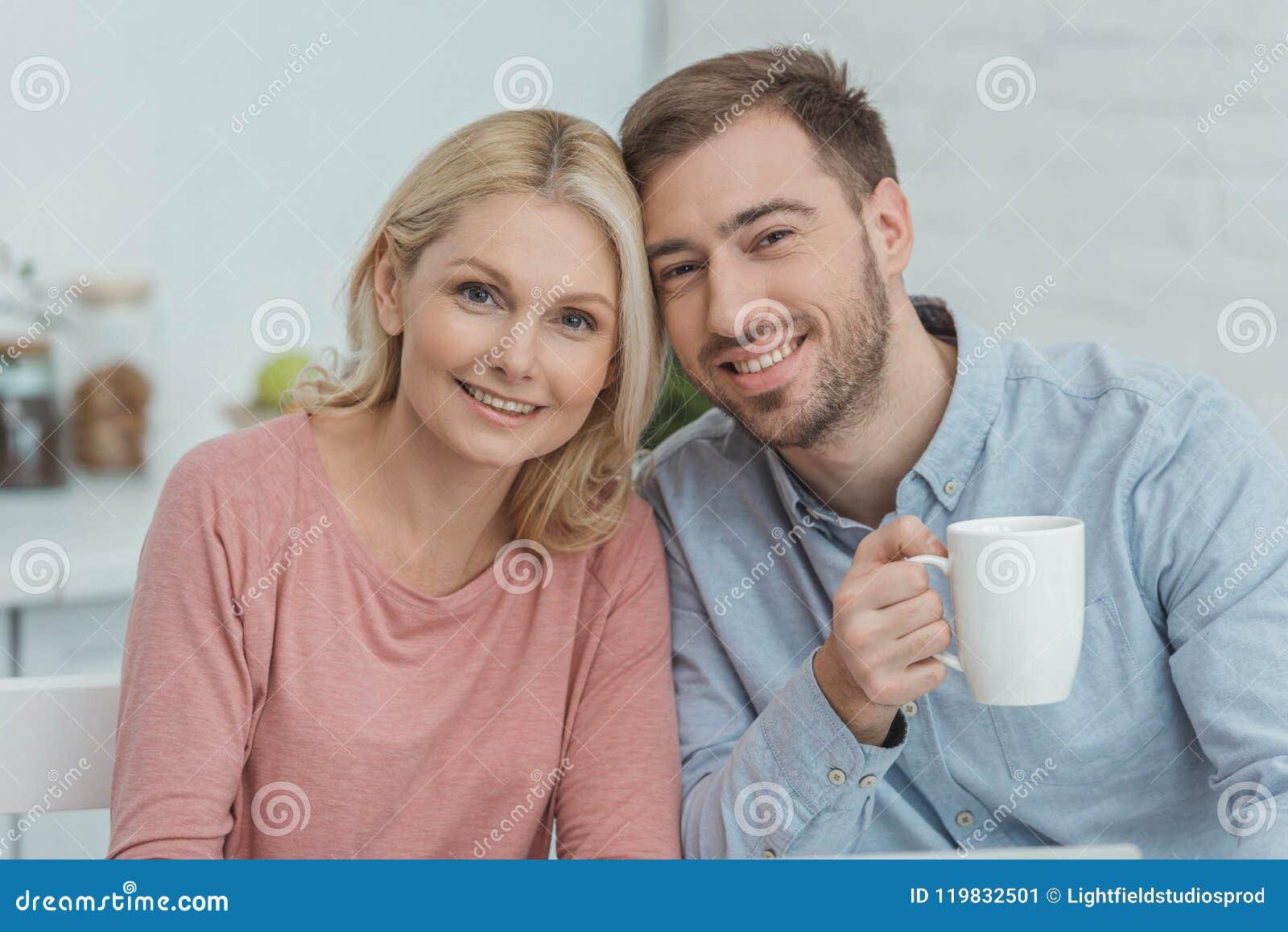Portret van glimlachende moeder en gekweekte zoon met kop van koffie het kijken
