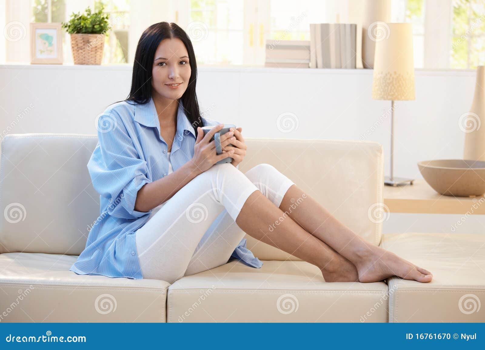 Portret van glimlachende vrouw die koffie op bank heeft