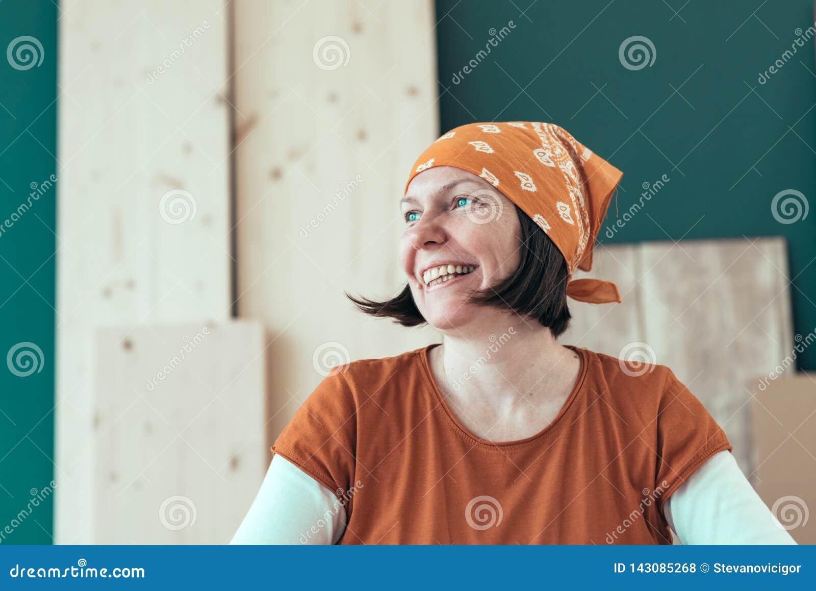 Portret van glimlachende vrouwelijke timmerman die headscarf bandana dragen