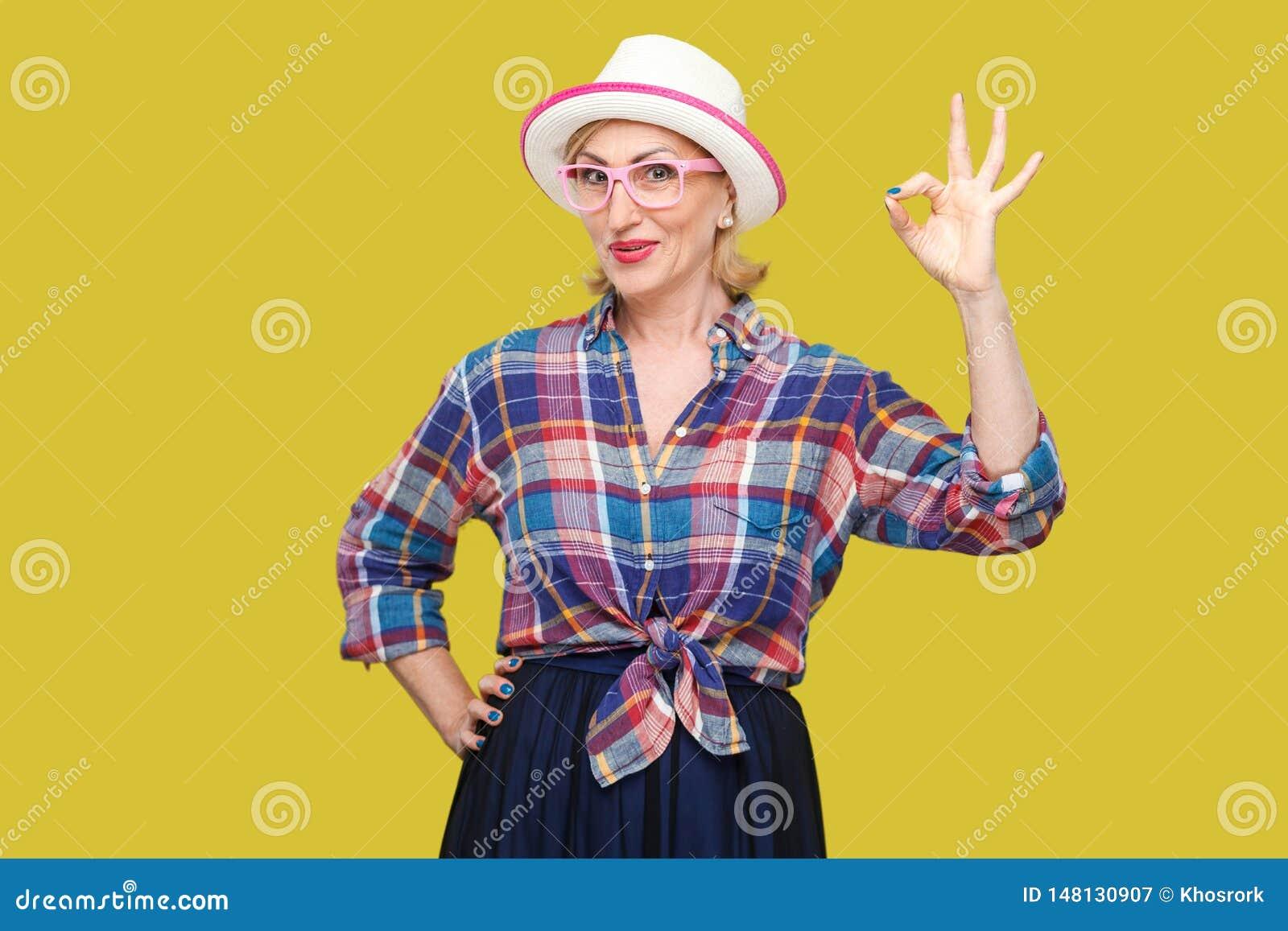 Portret van grappige gelukkige moderne leuke modieuze rijpe vrouw in toevallige stijl met hoed en oogglazen die zich met het O.k.