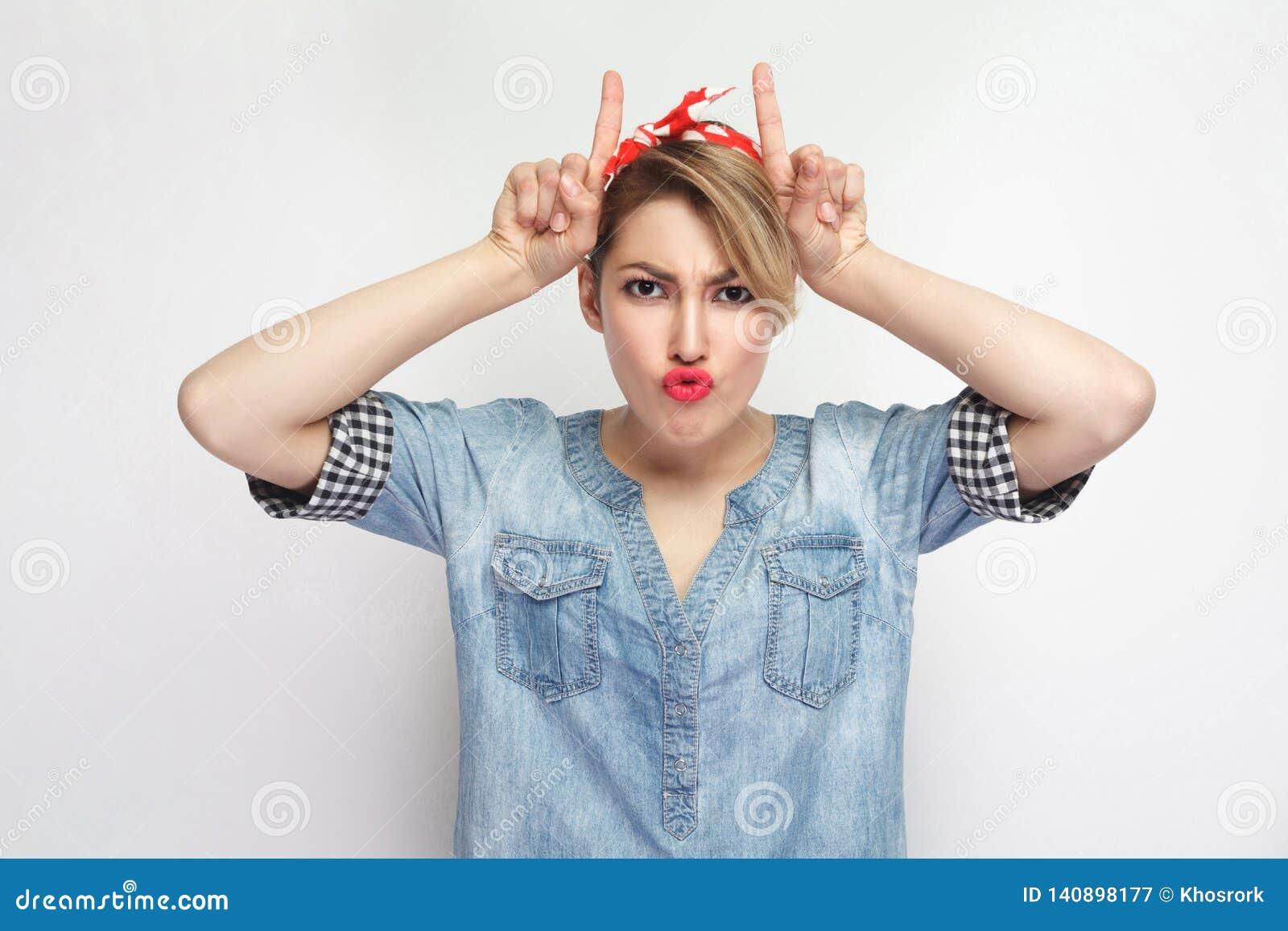 Portret van grappige mooie jonge vrouw in toevallig blauw denimoverhemd met make-up en rode hoofdband die zich met hoornenhanden