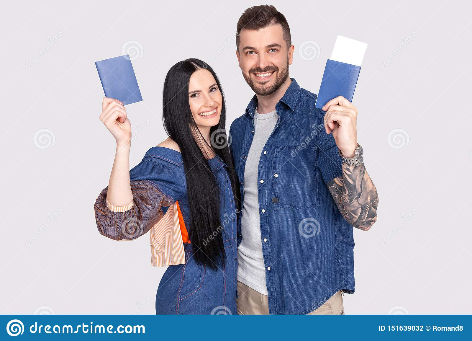 Portret van het blije blije paspoort van de paarholding met vliegende kaartjes in handen die worden geïsoleerd camera bekijken di