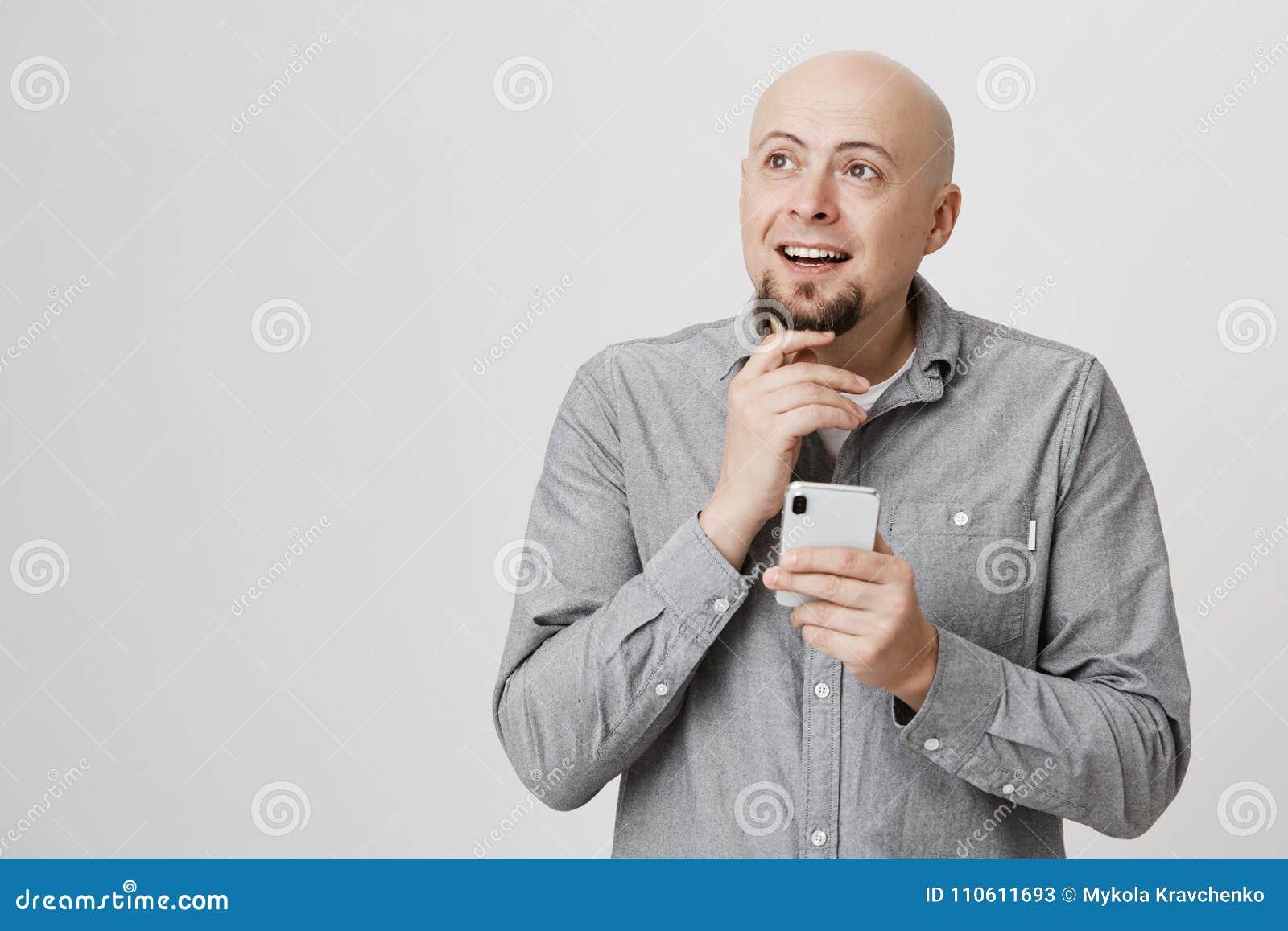 Portret van het charmeren van de kale Kaukasische volwassen mens wat betreft baard terwijl het houden van smartphone en het kijke