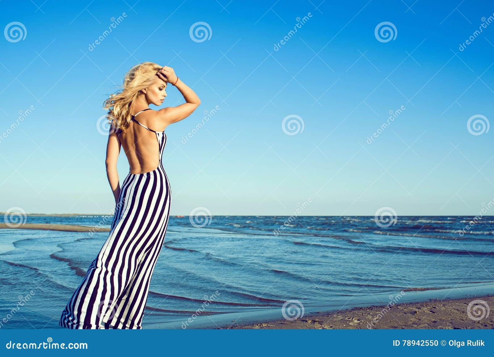 Portret van het charmeren van blonde langharige vrouw in lange zwart-witte gestreepte kleding met het naakte achter lopen langs d