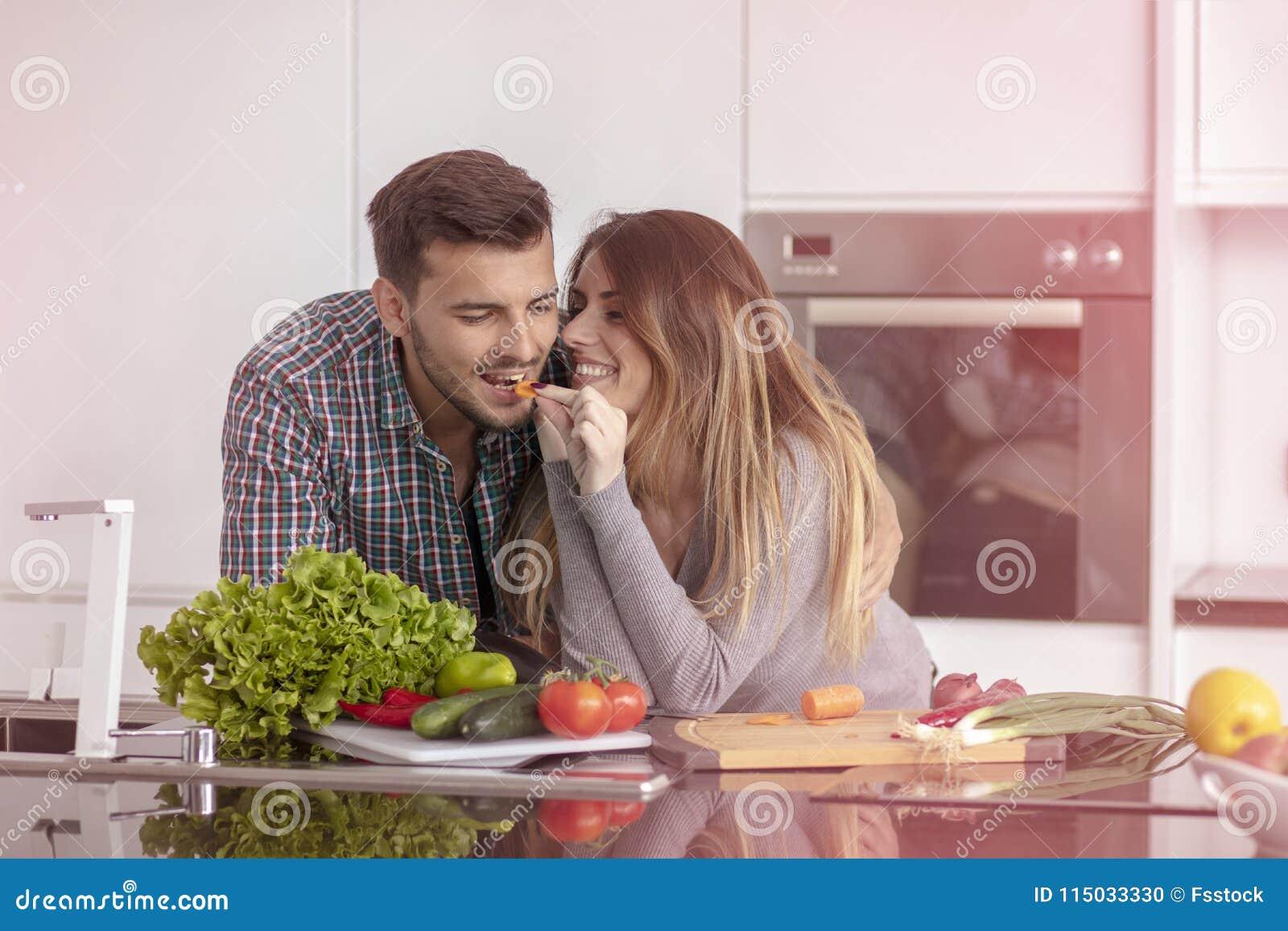 Portret van het gelukkige jonge paar koken samen in de keuken thuis