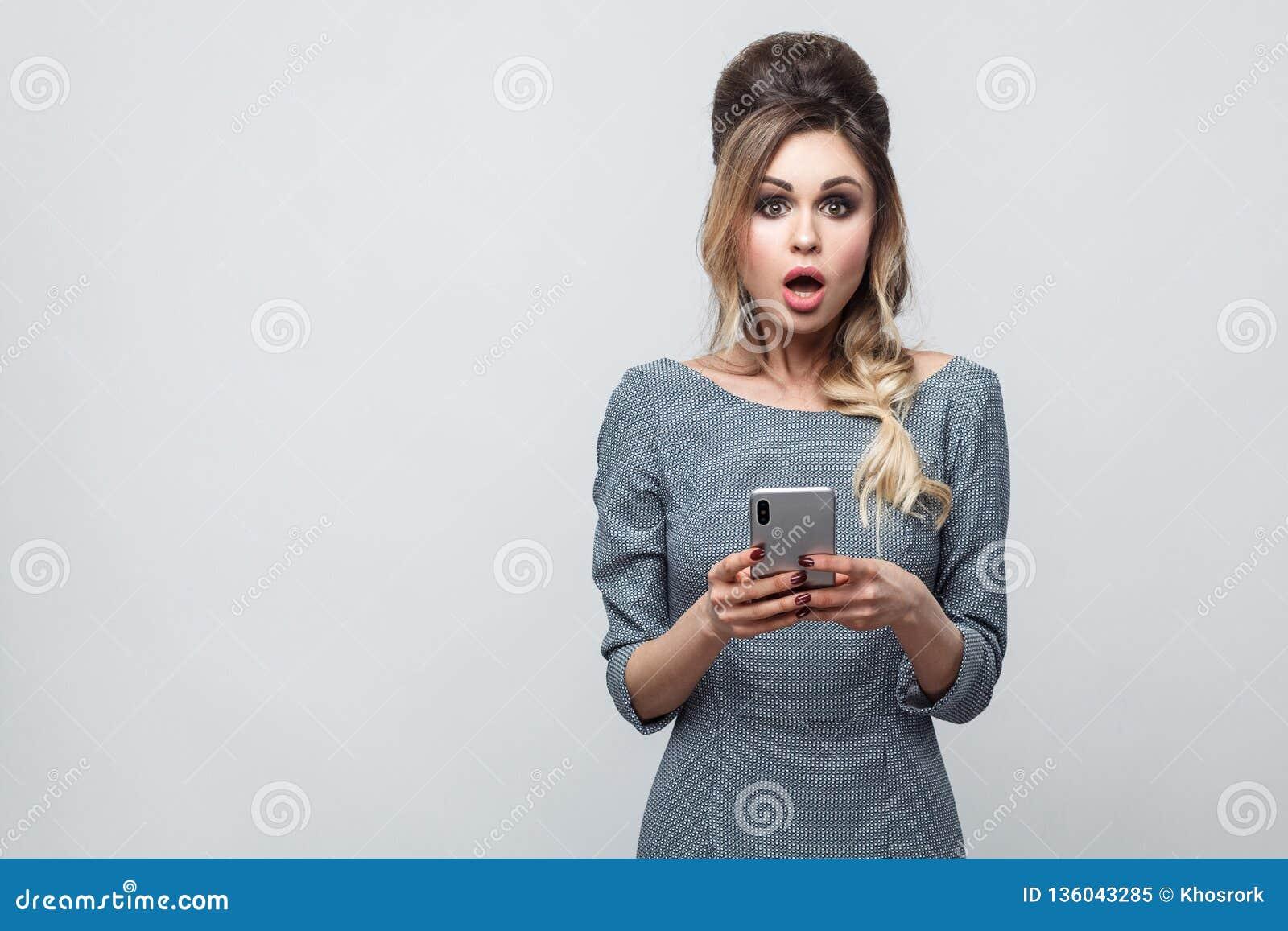 Portret van het geschokte mooie bloggertiener dragen in grijze kleding met vlecht bij hoofd status, het gebruiken van smartphone