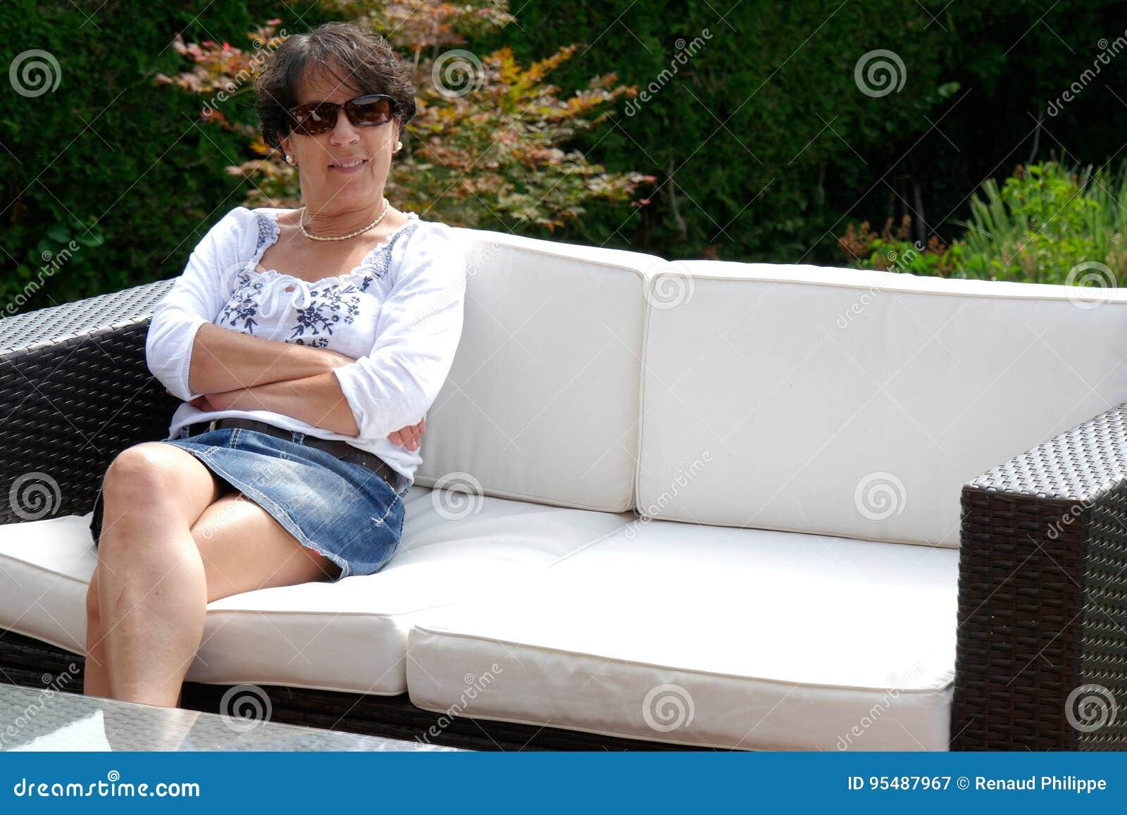 Portret van het glimlachen de zitting van de middenleeftijdsvrouw in tuin thuis