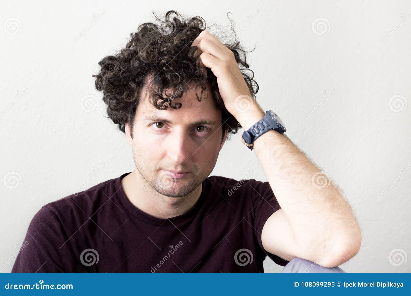 Portret van het jonge, Kaukasische, donkerbruine, krullende haired mens kijken