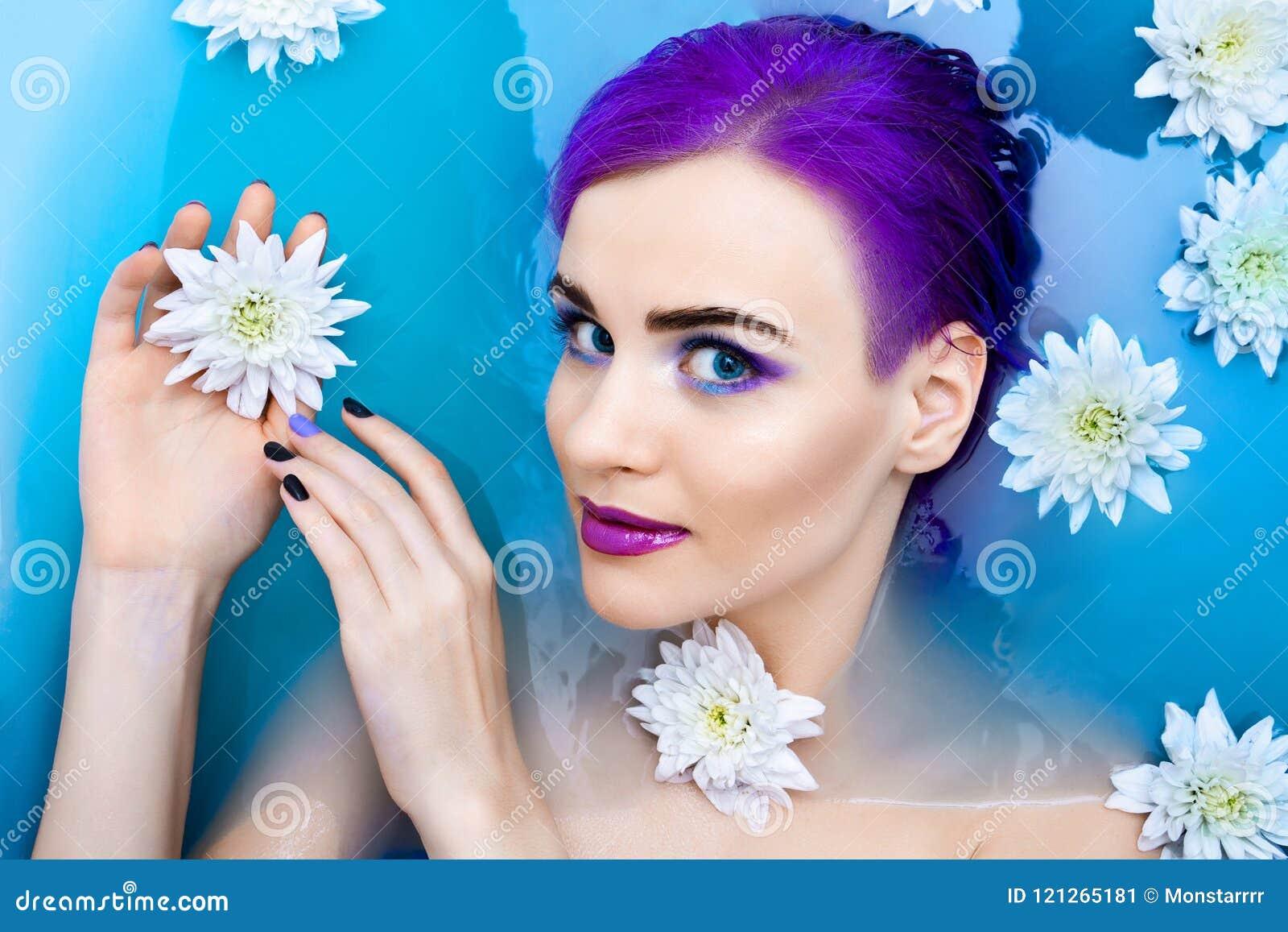 Portret van het jonge leuke vrouwelijke model van de manierluxe in badkuip met bloemen