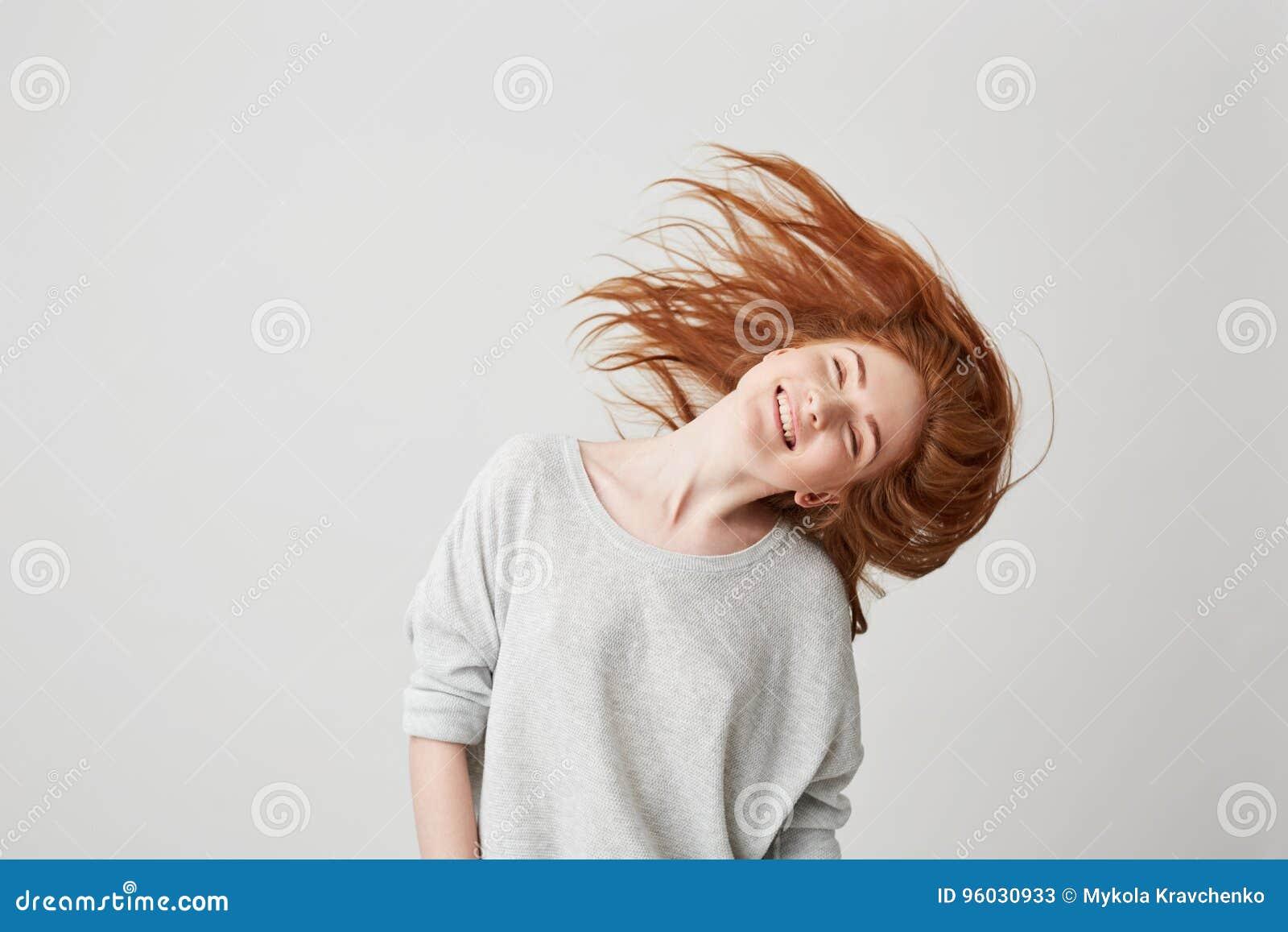 Portret van het jonge vrolijke mooie roodharigemeisje glimlachen met gesloten ogen die hoofd en haar over witte achtergrond schud