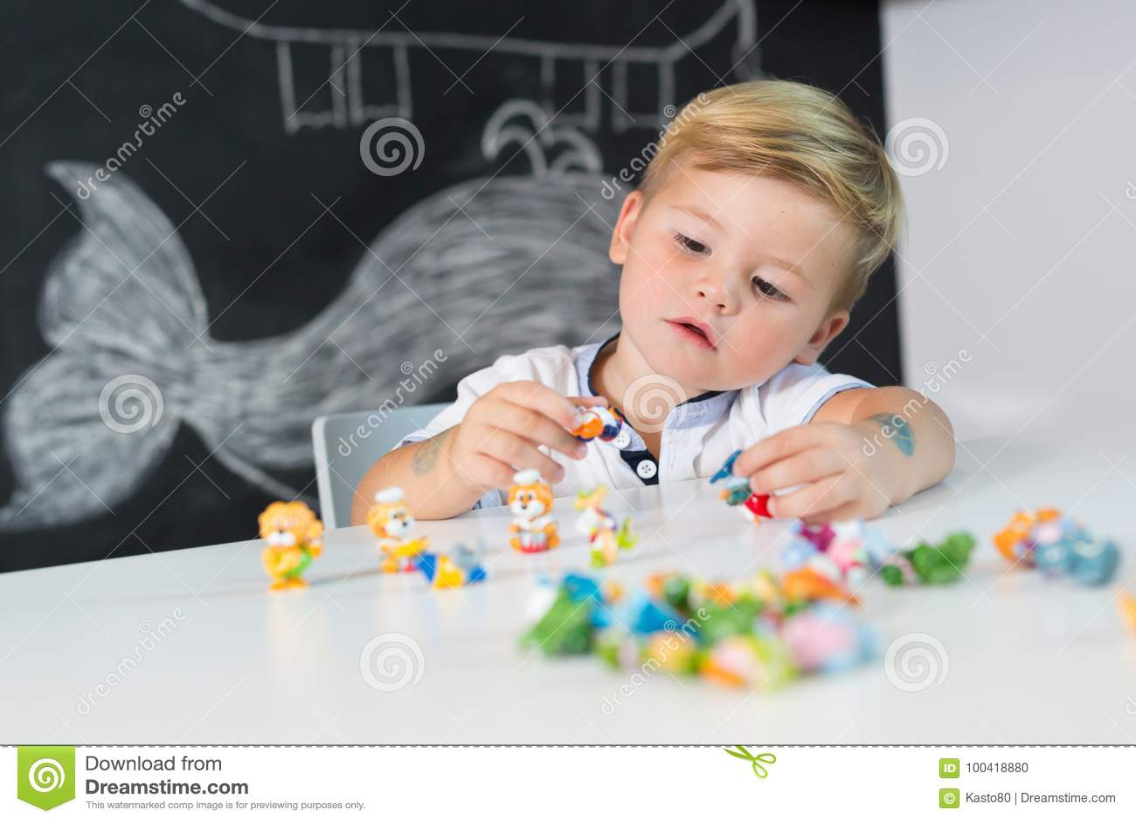 Portret van het leuke peuterjongen spelen met speelgoed bij het bureau thuis