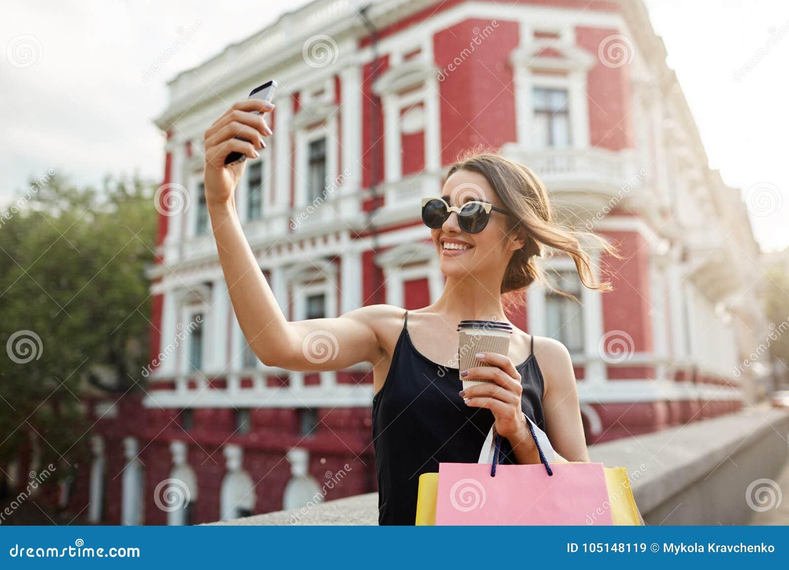Portret van jong aantrekkelijk vrouwelijk Kaukasisch meisje die met donker haar in tan glazen en zwarte kleding helder glimlachen