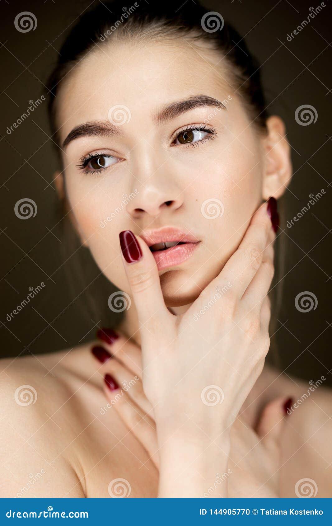 Portret van jong charmant meisje die met natuurlijke make-up haar handen op haar gezicht houden