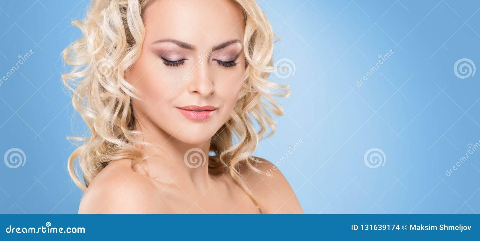Portret van jong en mooi blond meisje met krullend haar Gezicht het opheffen en schoonheidsconcept