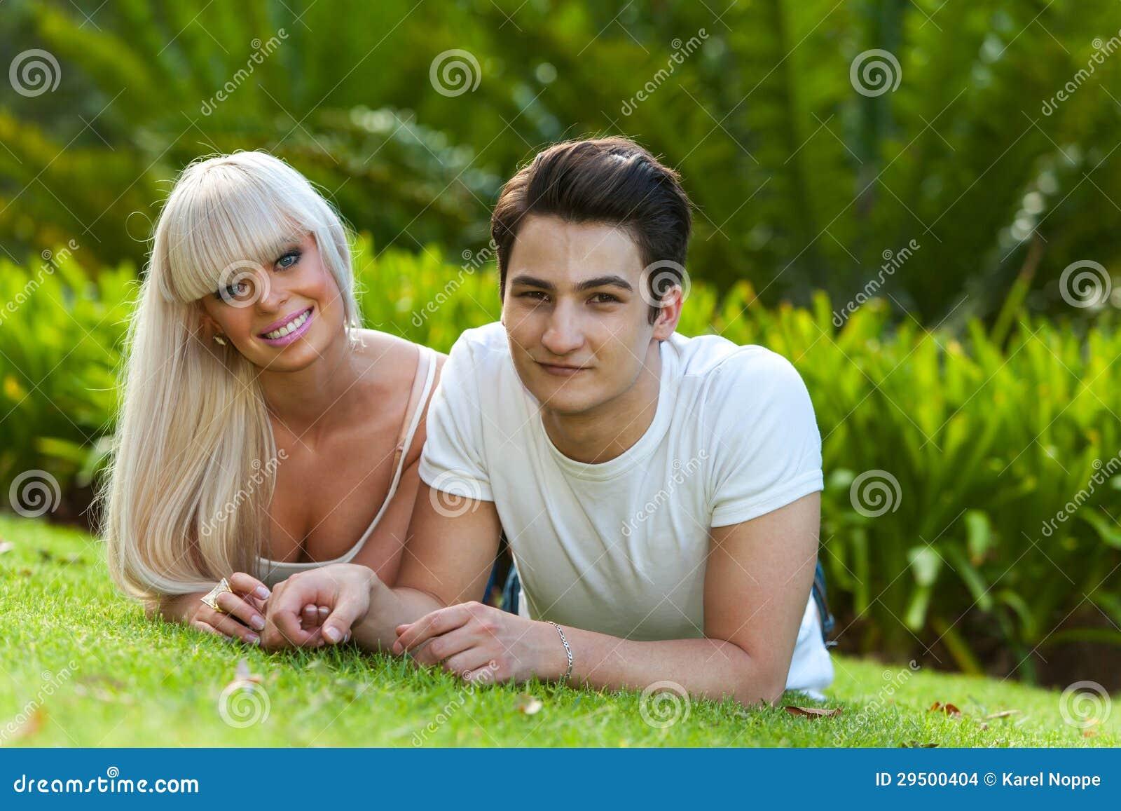 Portret van jong paar die op groen gras leggen.