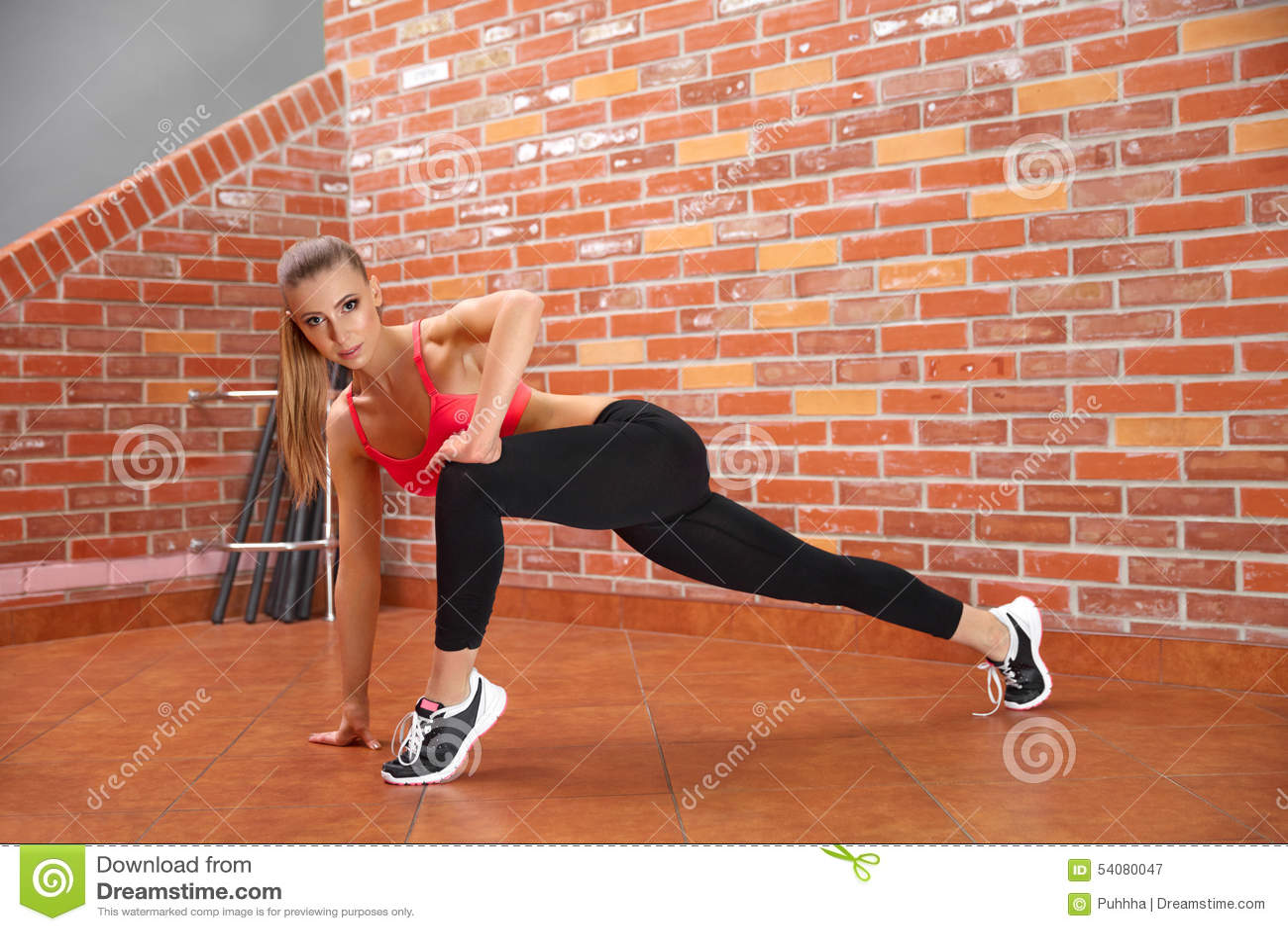 Portret van jong sportief meisje die uitrekkende oefening doen