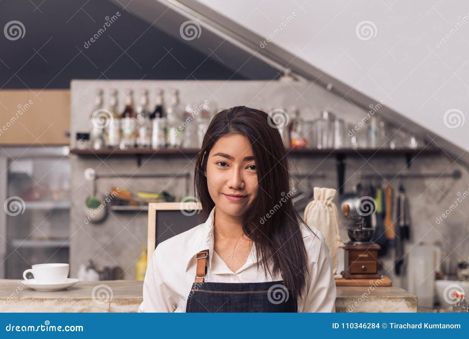 Portret van jonge Aziatische vrouwelijke barista die haar klant in koffiewinkel met een achtergrond van de teller van de drankbar