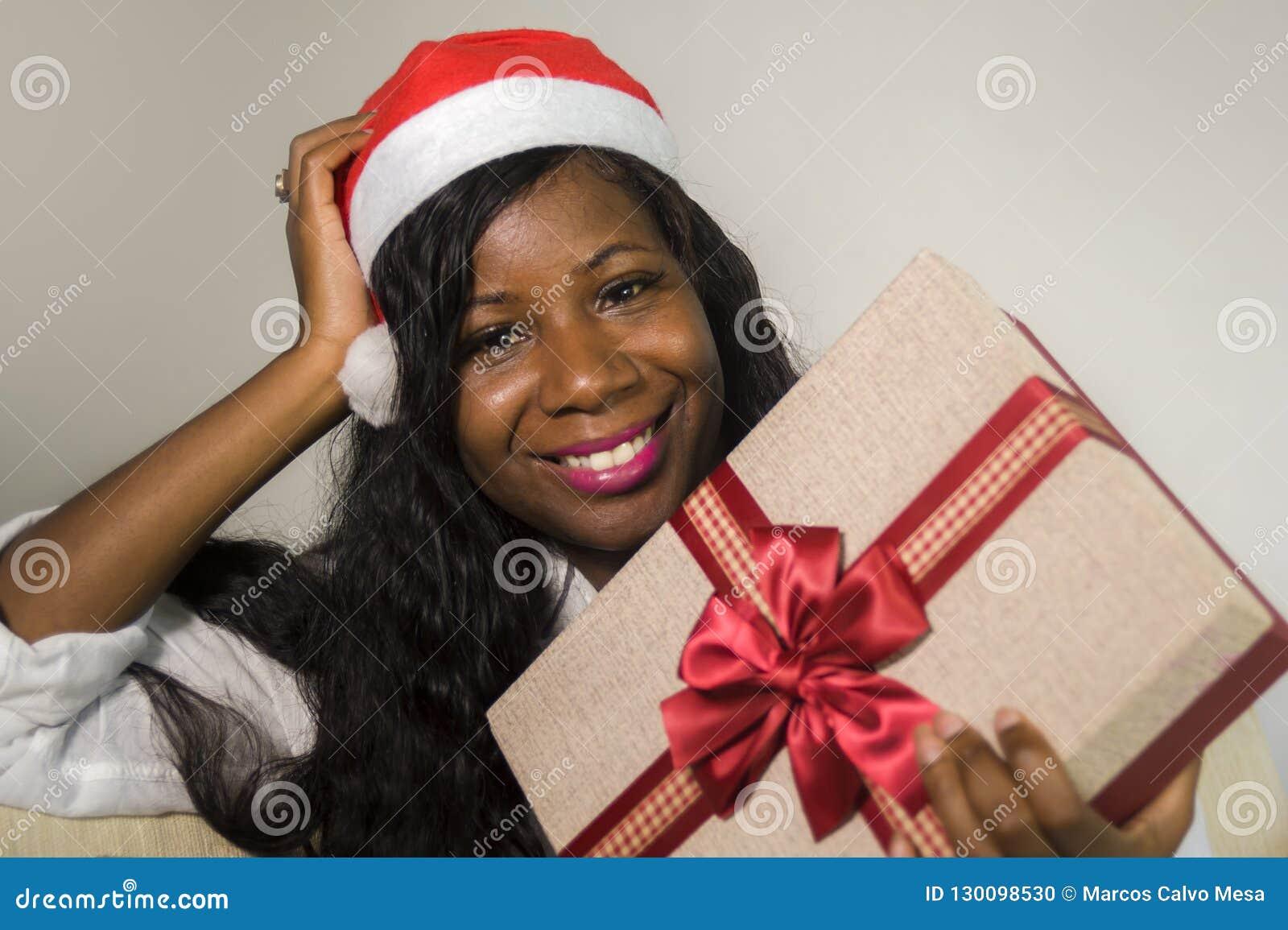 Portret van jonge gelukkige en mooie zwarte Afrikaanse Amerikaanse vrouw die in Santa Claus-hoed het huidige doos glimlachen houd