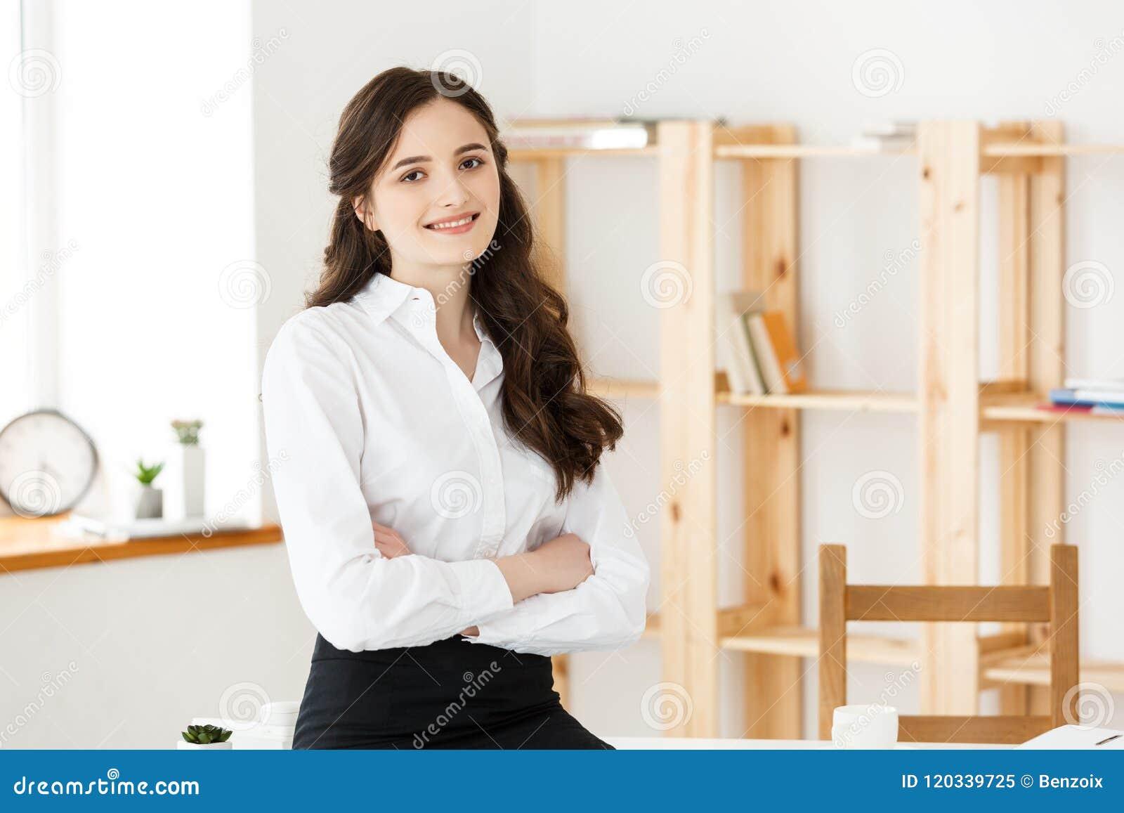 Portret van jonge mooie bedrijfsvrouw in het bureau Smilling en Gekruiste wapens
