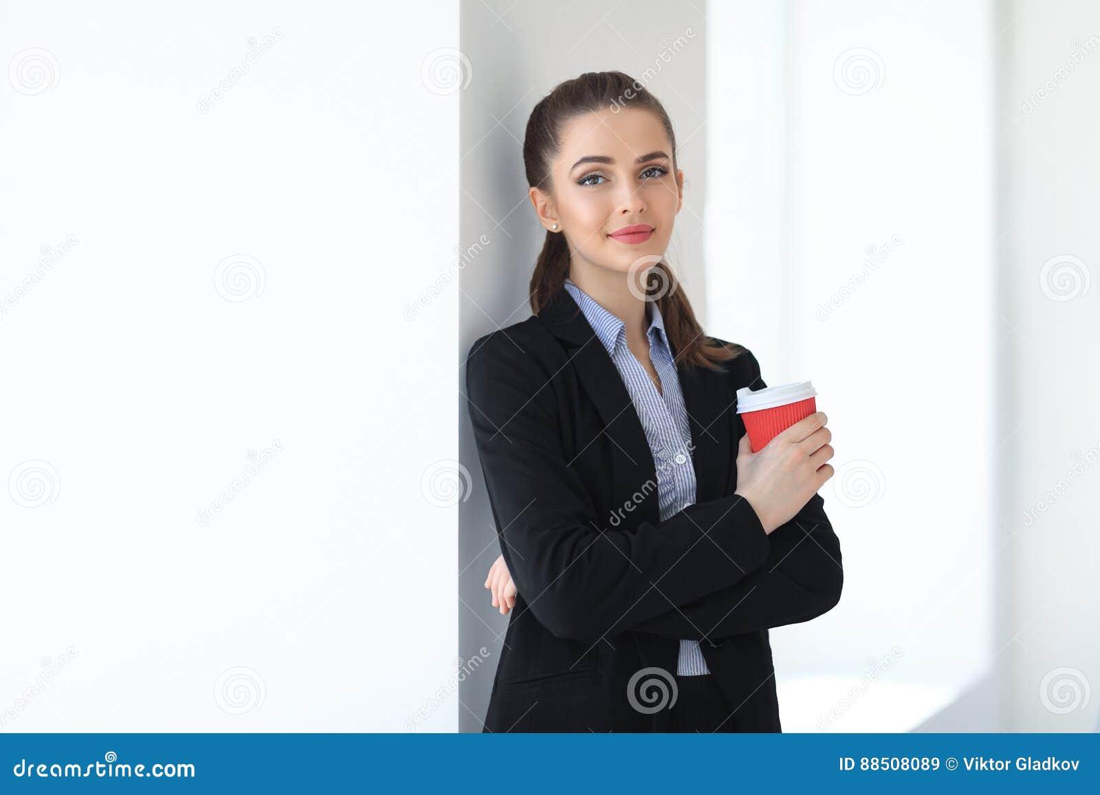 Portret van jonge mooie bedrijfsvrouw met binnen kop van koffie