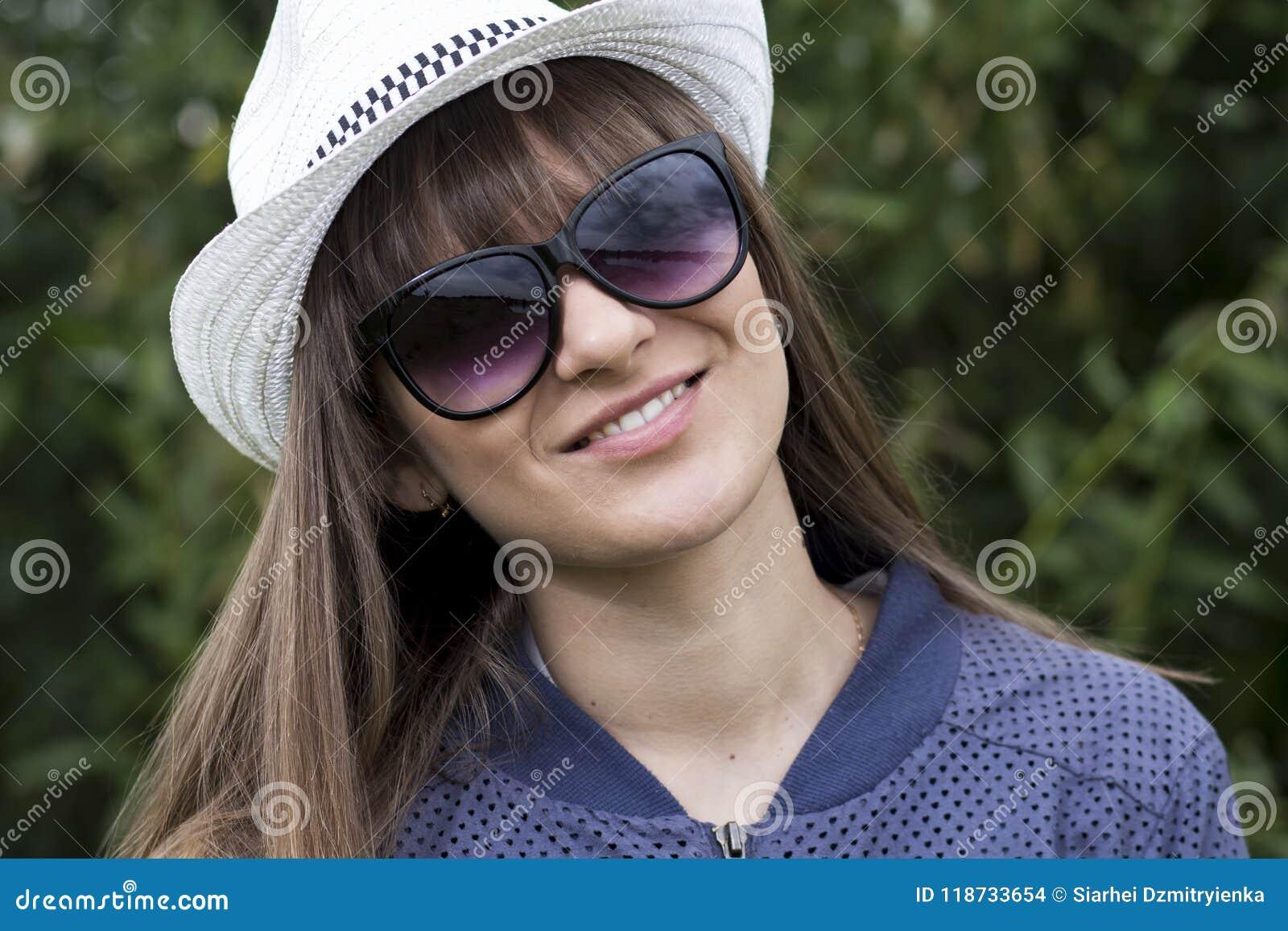 Portret van jonge mooie tiener in hoed en zonnebril in de zomerpark Gelukkig glimlachend leuk meisje op groene aardachtergrond