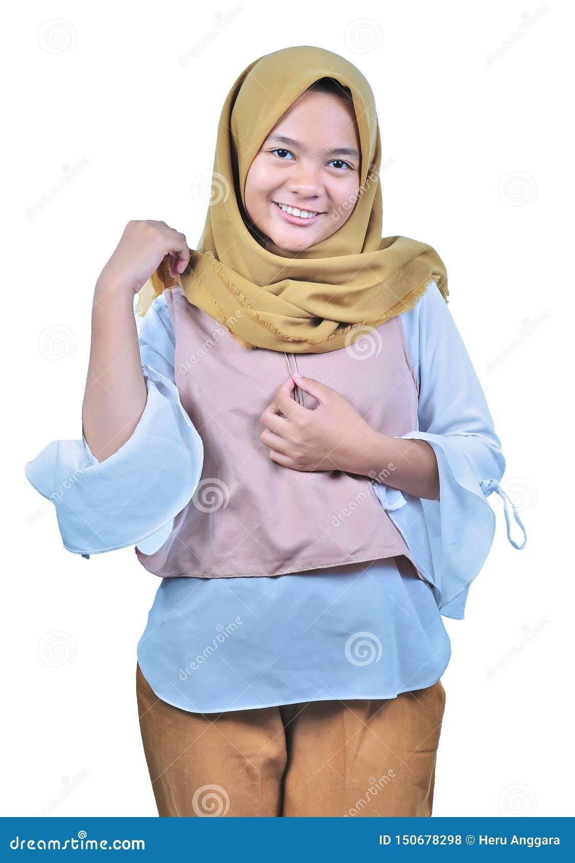 Portret van jonge moslimvrouw in hijab die en camera glimlachen bekijken Een jonge Moslim gelukkige vrouw