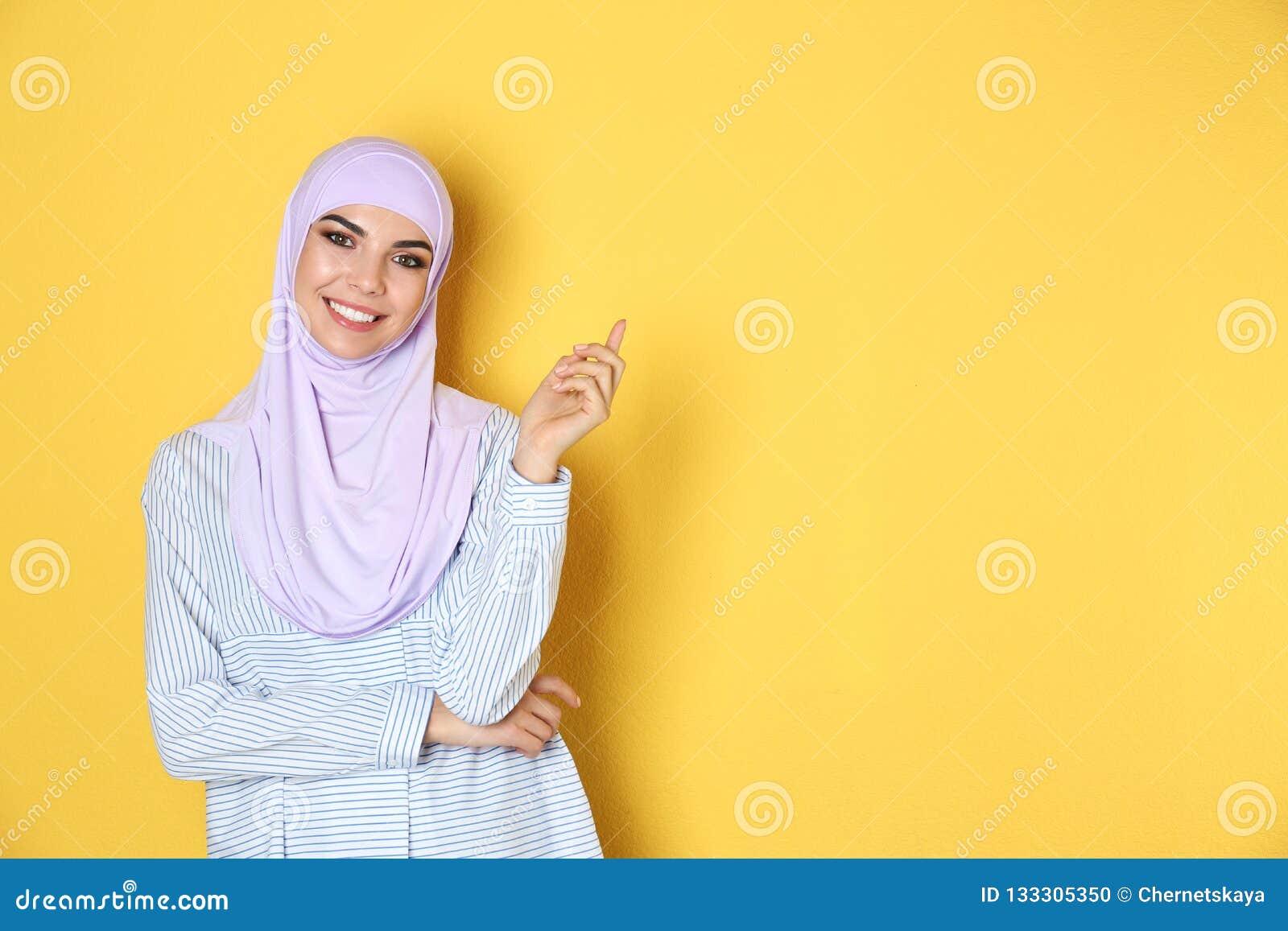 Portret van jonge Moslimvrouw in hijab tegen kleurenachtergrond