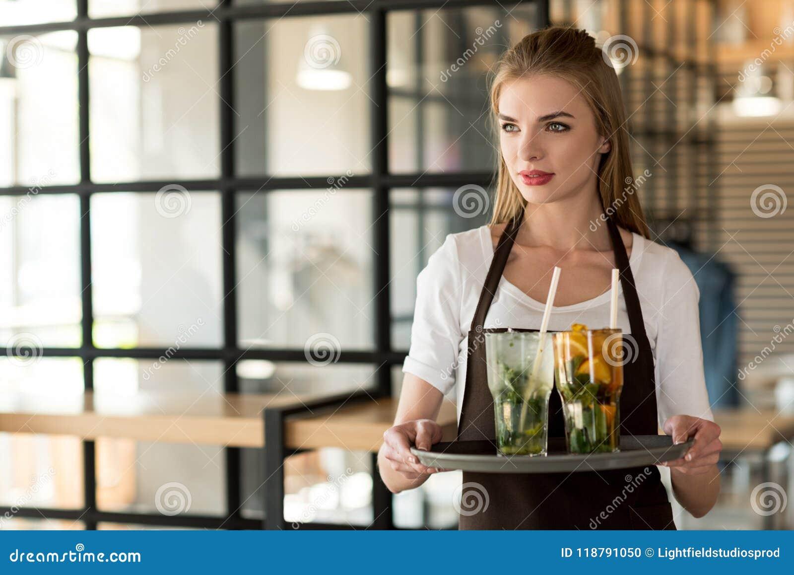Portret van jonge serveerster in het dienblad van de schortholding met het verfrissen van dranken