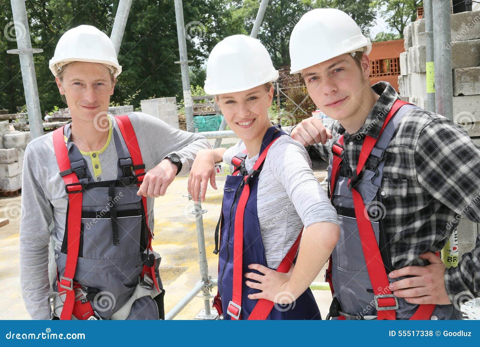 Portret van jongeren met helmen in bouw