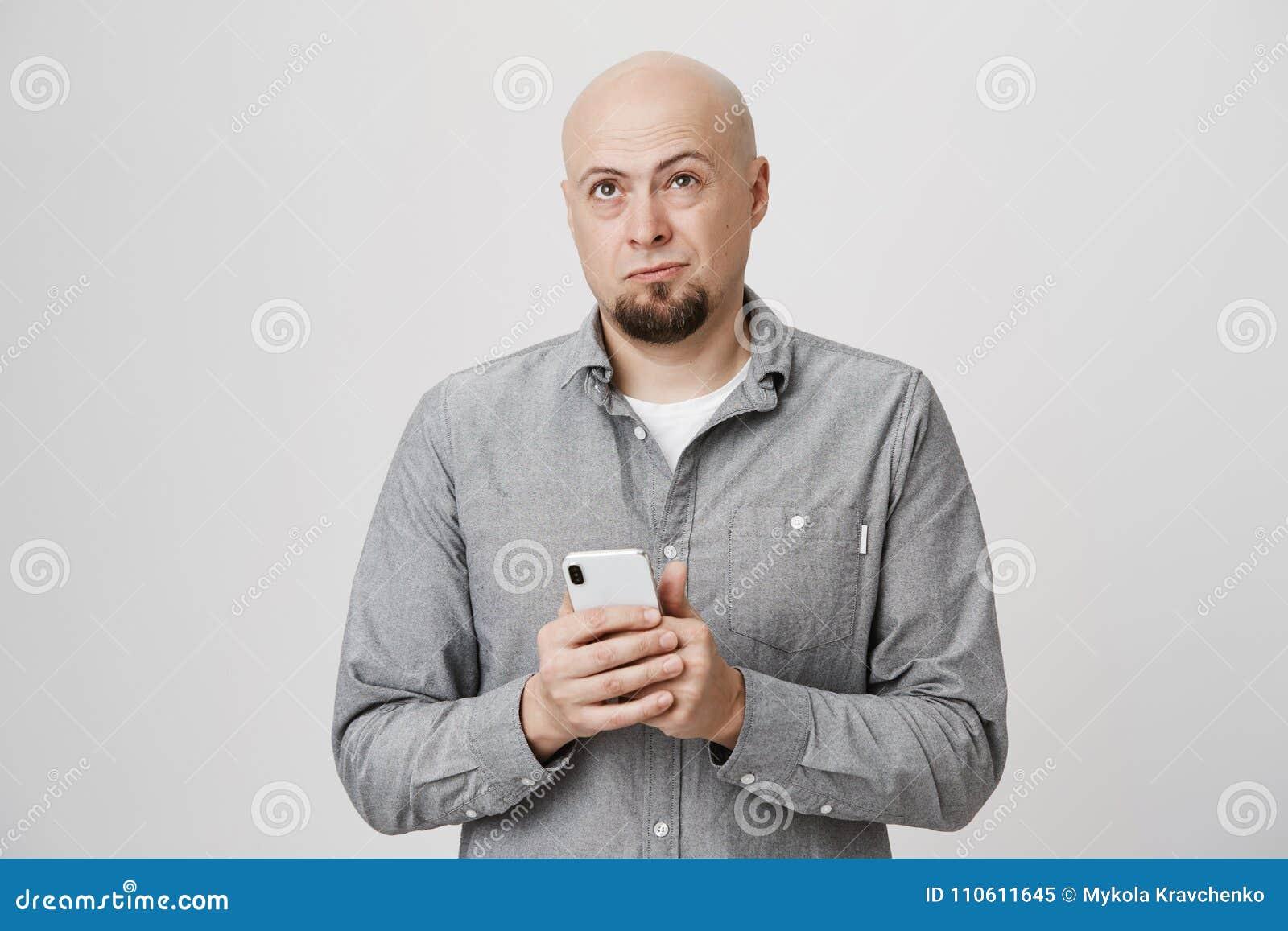 Portret van knappe kale Europese smartphone van de kerelholding terwijl omhoog het fronsen en kijken die, telefoon aan aantal pro