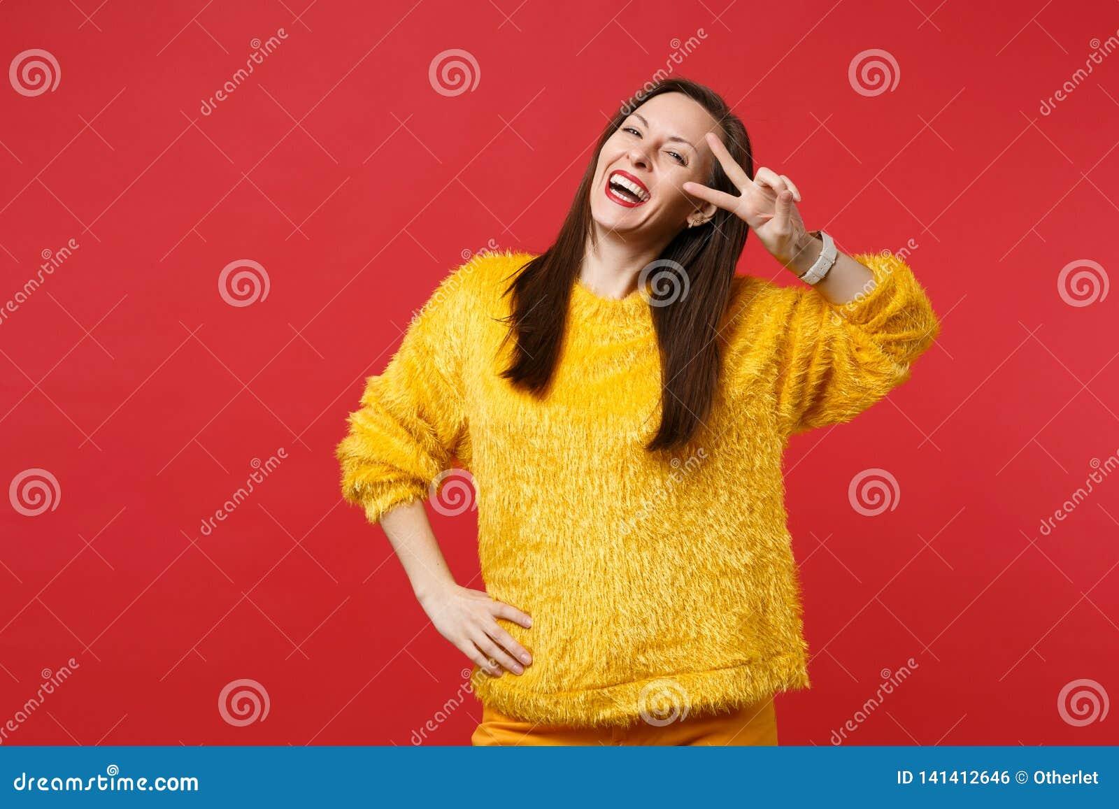 Portret van lachende grappige jonge vrouw in gele bontsweater die die overwinningsteken tonen op heldere rode muurachtergrond wor