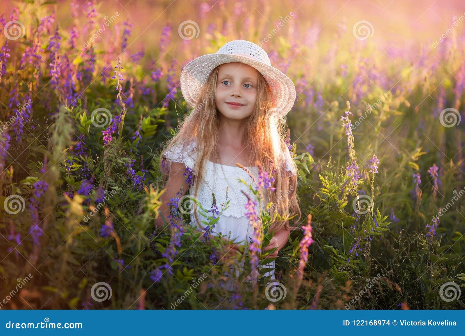 Portret van leuk jong meisje met lang haar in een hoed bij zonsondergang