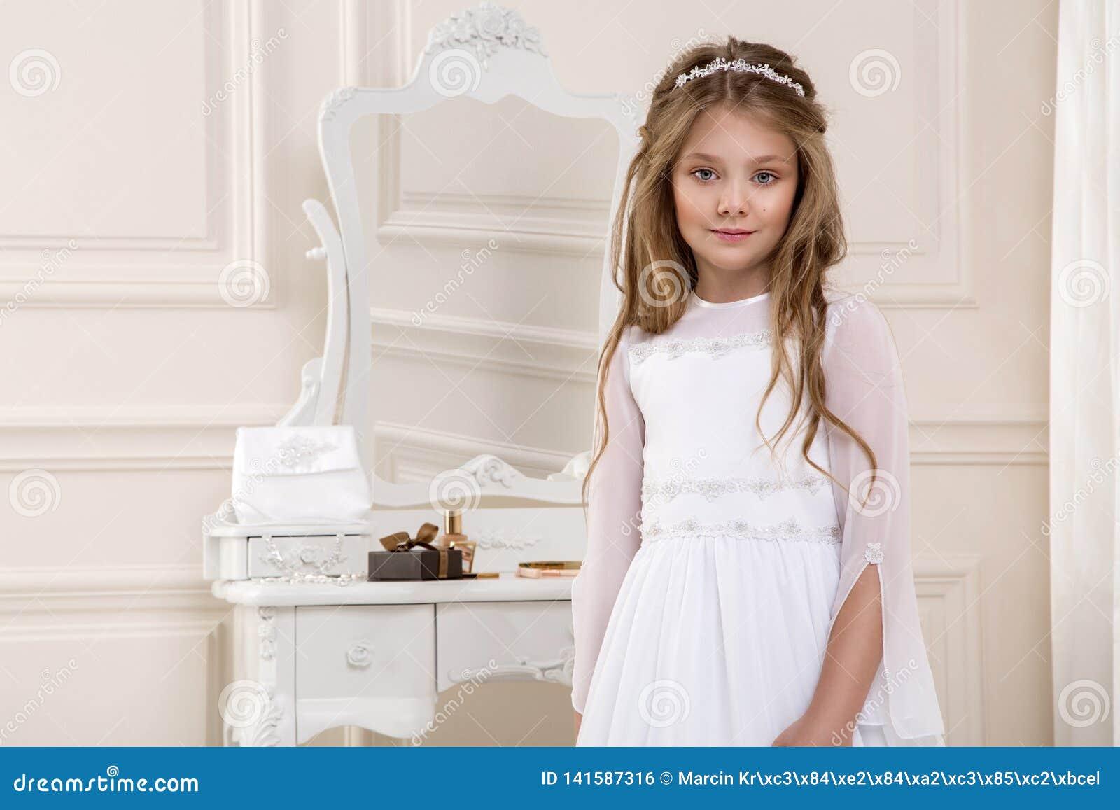 Portret van leuk meisje op witte kleding en kroon op eerste heilige kerkgemeenschap achtergrondkerkpoort