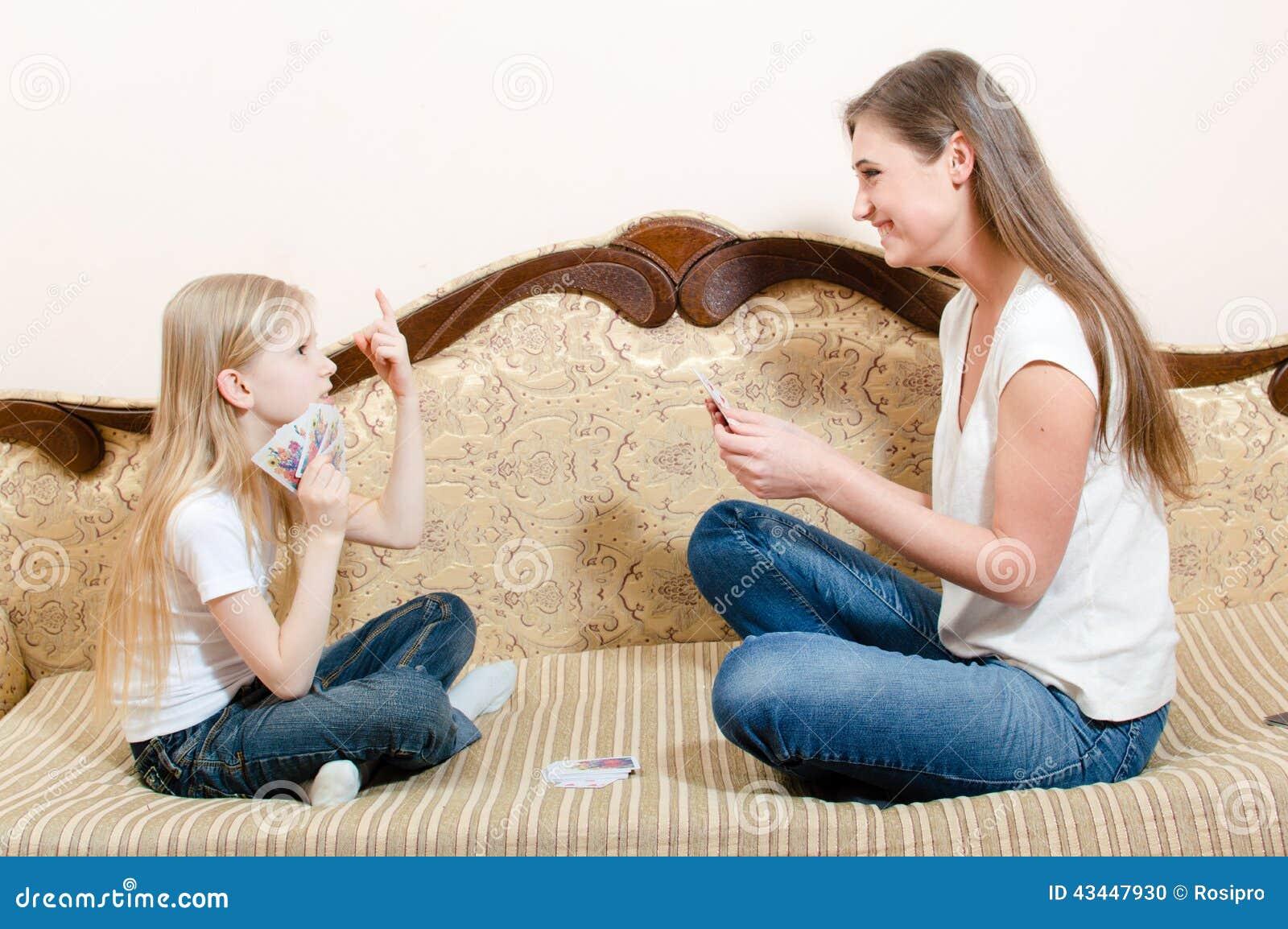 Portret van leuk weinig blond jong geitjemeisje en mooie donkerbruine jonge vrouw die pret gelukkige het glimlachen speelkaarten