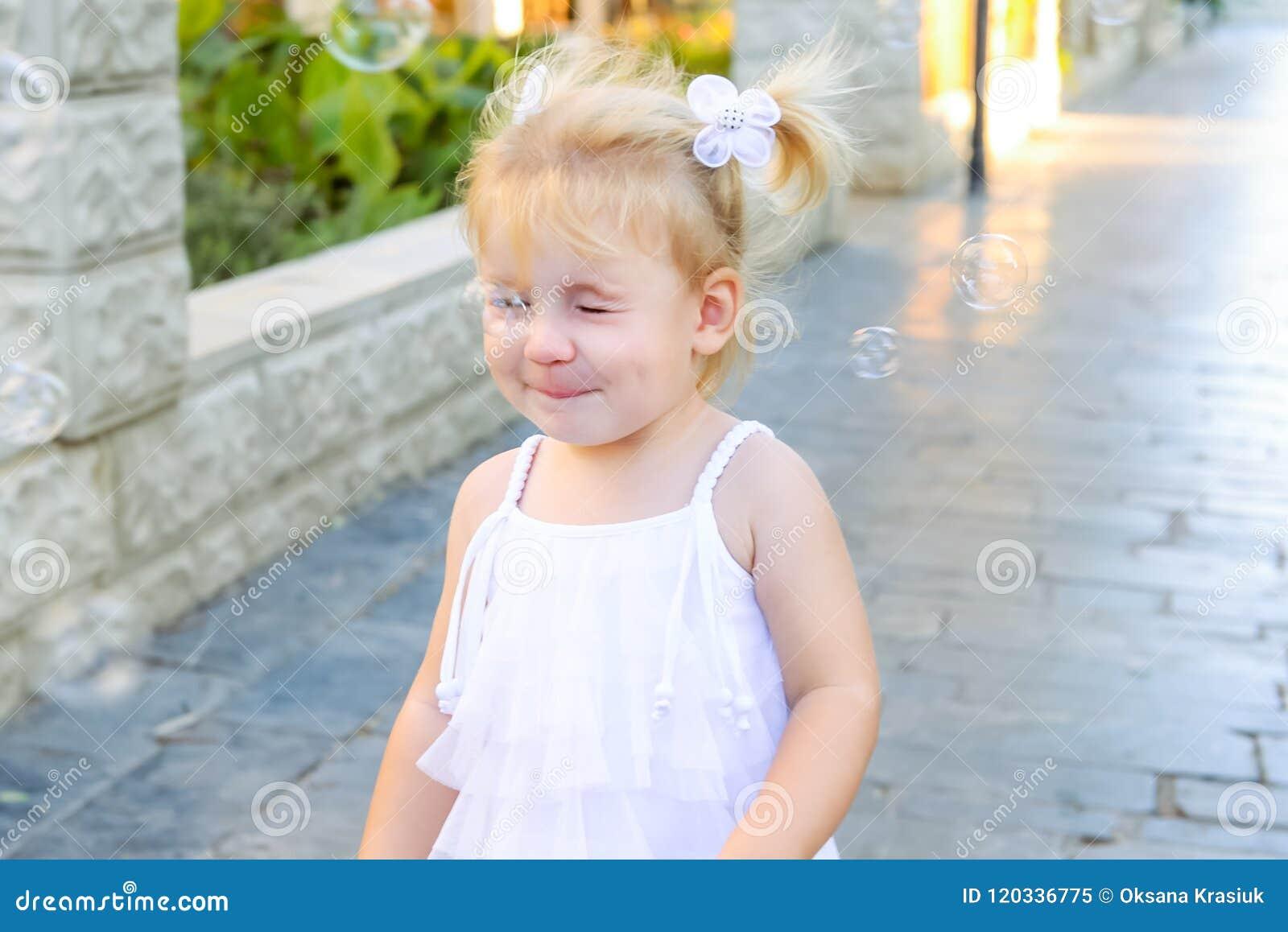 Portret van leuk weinig emotioneel blondy peutermeisje in kleding met zeepbels het breken van haar neus Gang in het stadspark act
