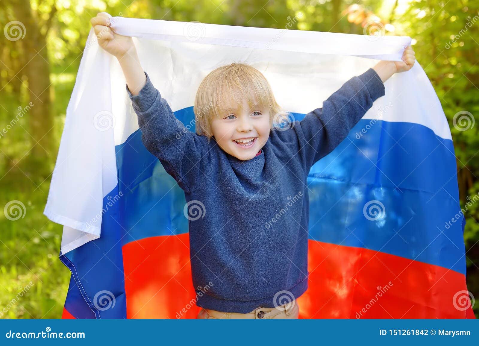 Portret van leuk weinig jongen in openbaar de zomerpark met Russische vlag op achtergrond Ondersteunend en hun ventilatorskind di
