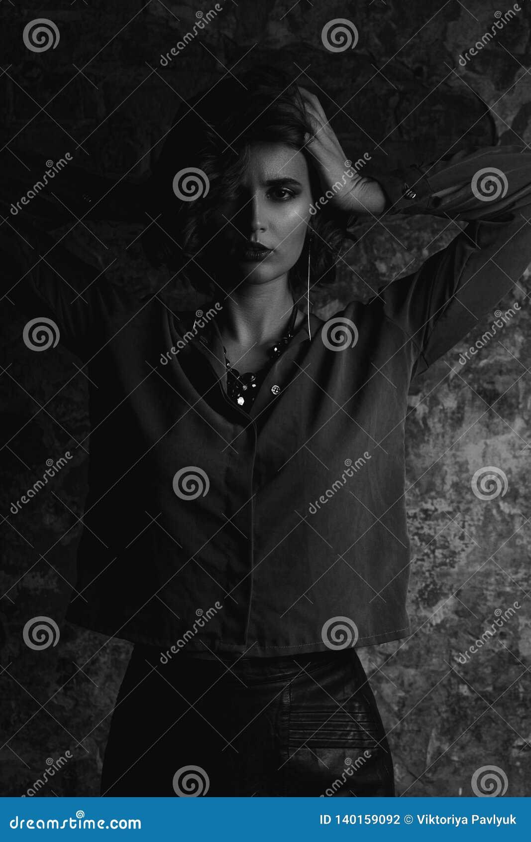 Portret van luxueus donkerbruin meisje met golfhaar het stellen met contrastlicht Het zwart-witte stemmen