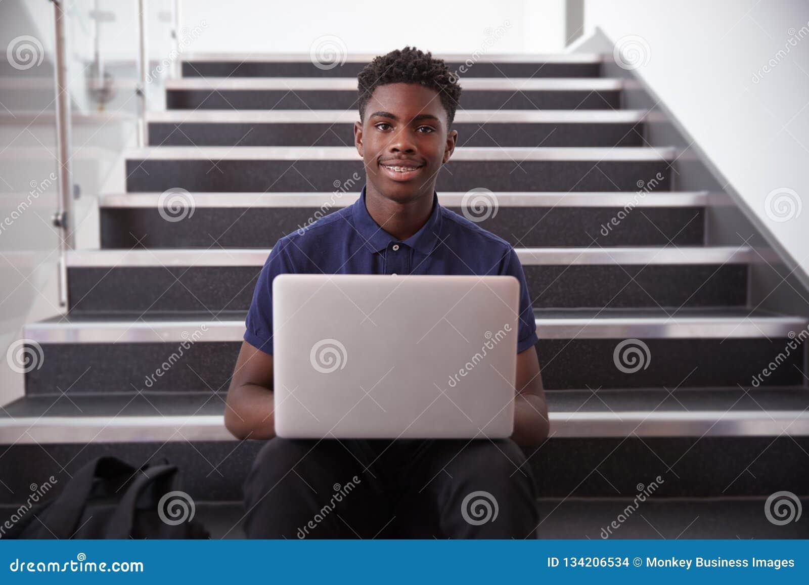 Portret van Mannelijke Middelbare schoolstudent Sitting On Staircase en het Gebruiken van Laptop