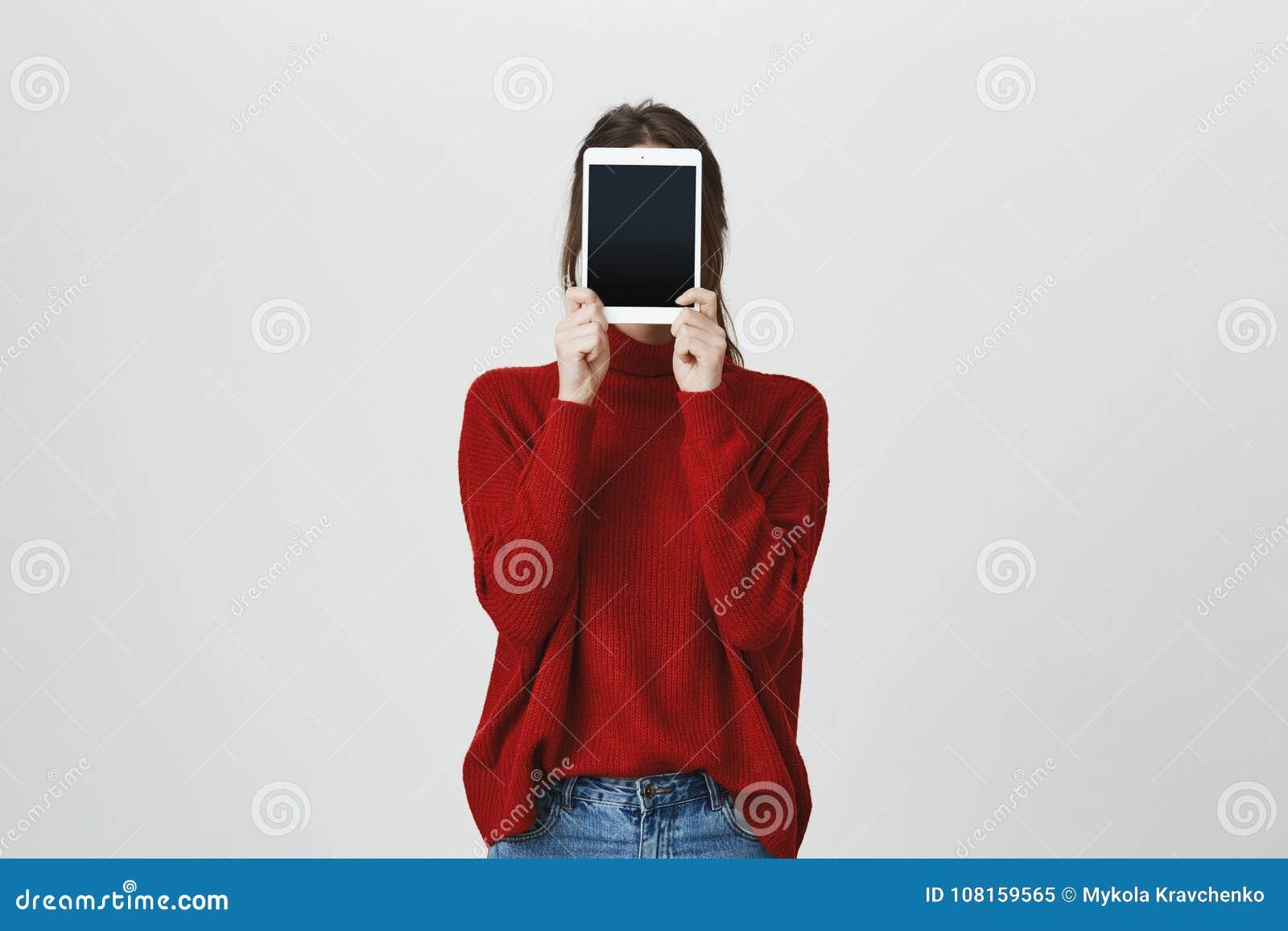 Portret van meisje in in rode sweater die haar gezicht behandelen met een tablet die zich dichtbij witte muur bevinden Technologi