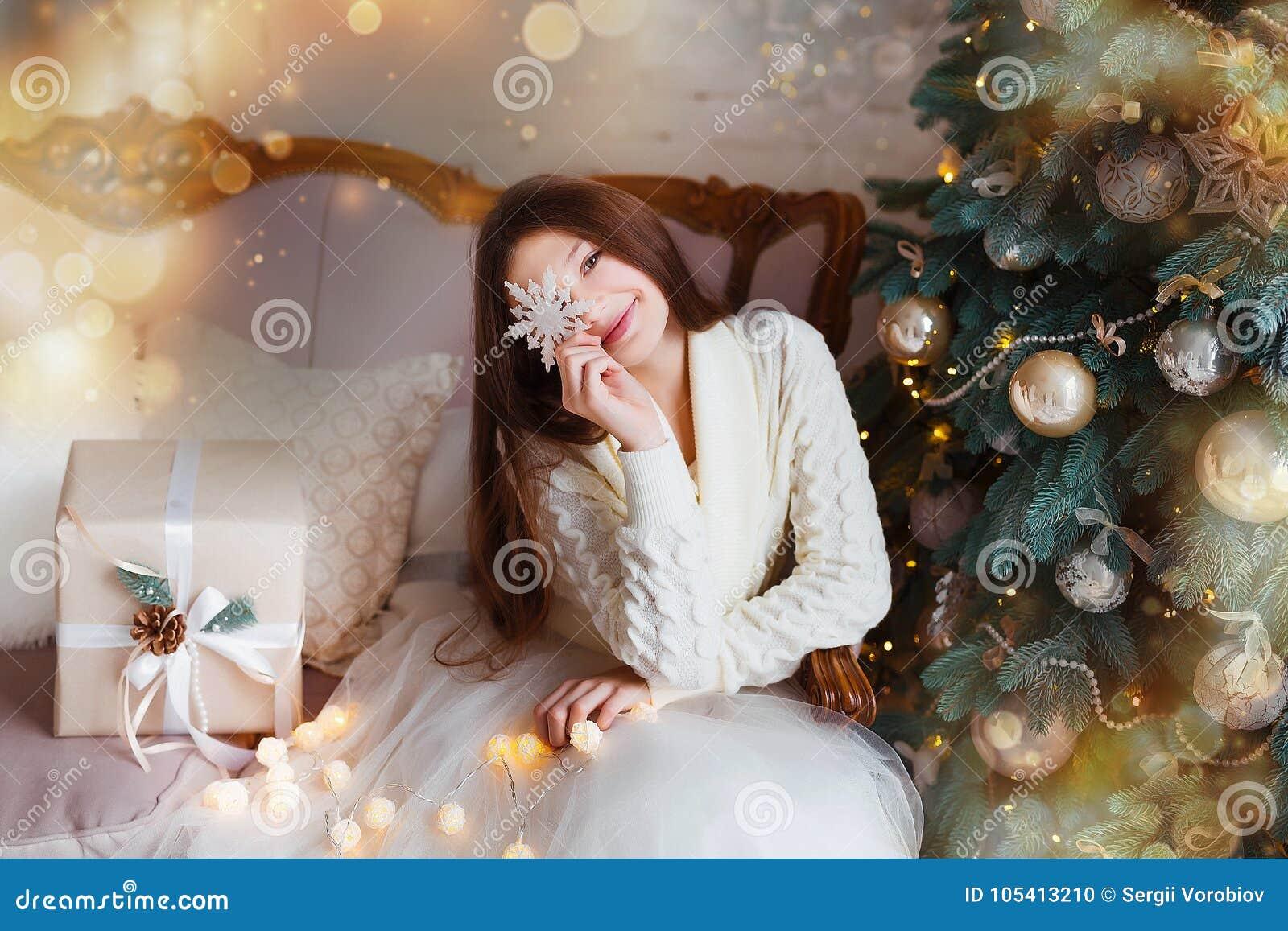 Portret van mooi meisje met lang haar die warme de winterkleren in Kerstmisbinnenland dragen