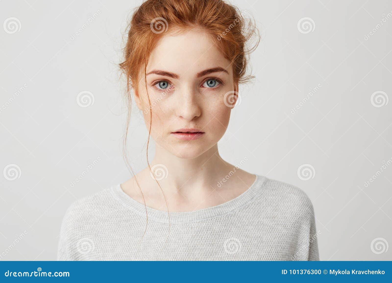 Portret van mooi teder gembermeisje met het blauwe ogen stellen die camera over witte achtergrond bekijken