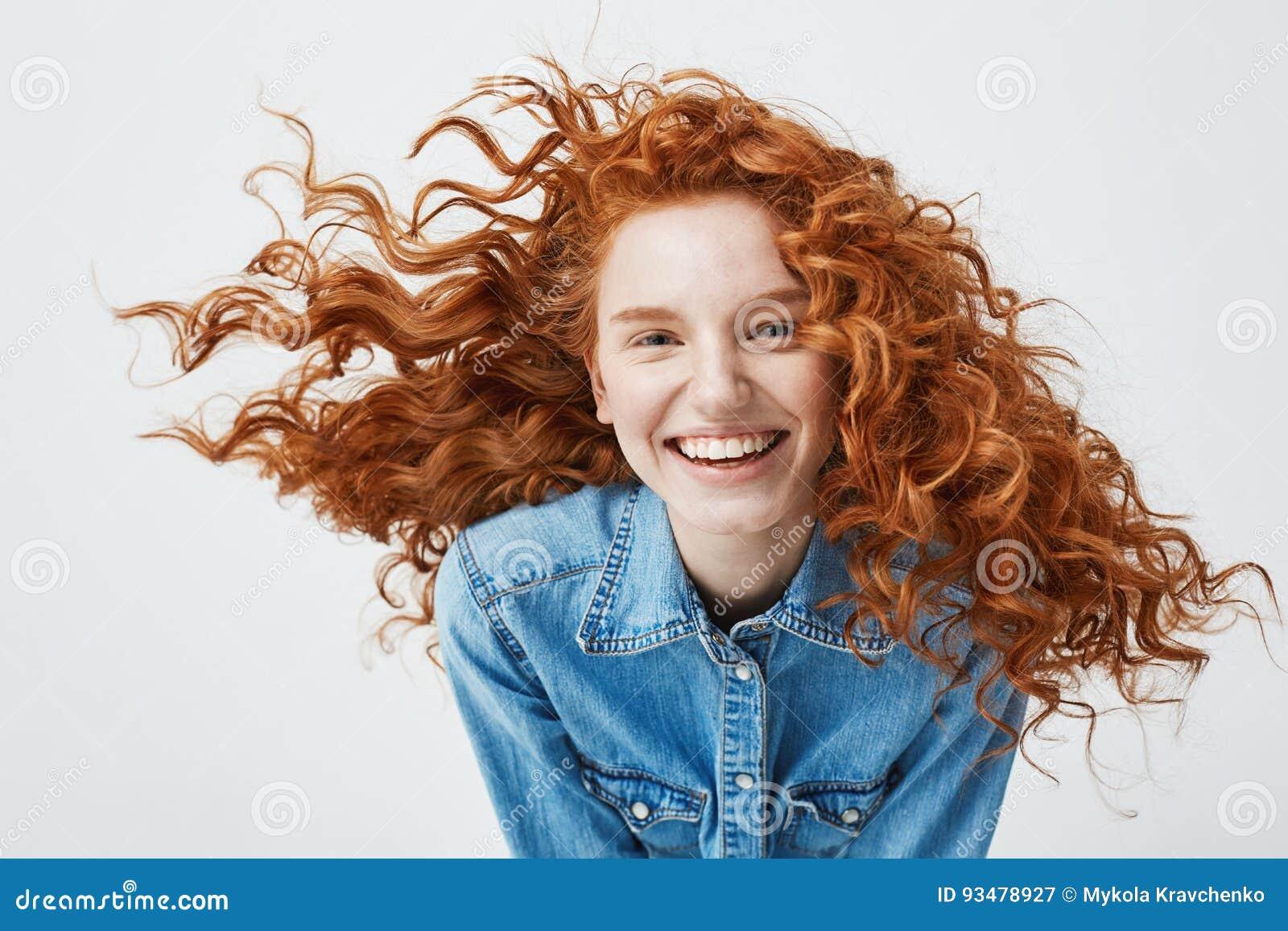 Portret van mooi vrolijk roodharigemeisje met het vliegen het krullende haar het glimlachen het lachen bekijken camera over wit